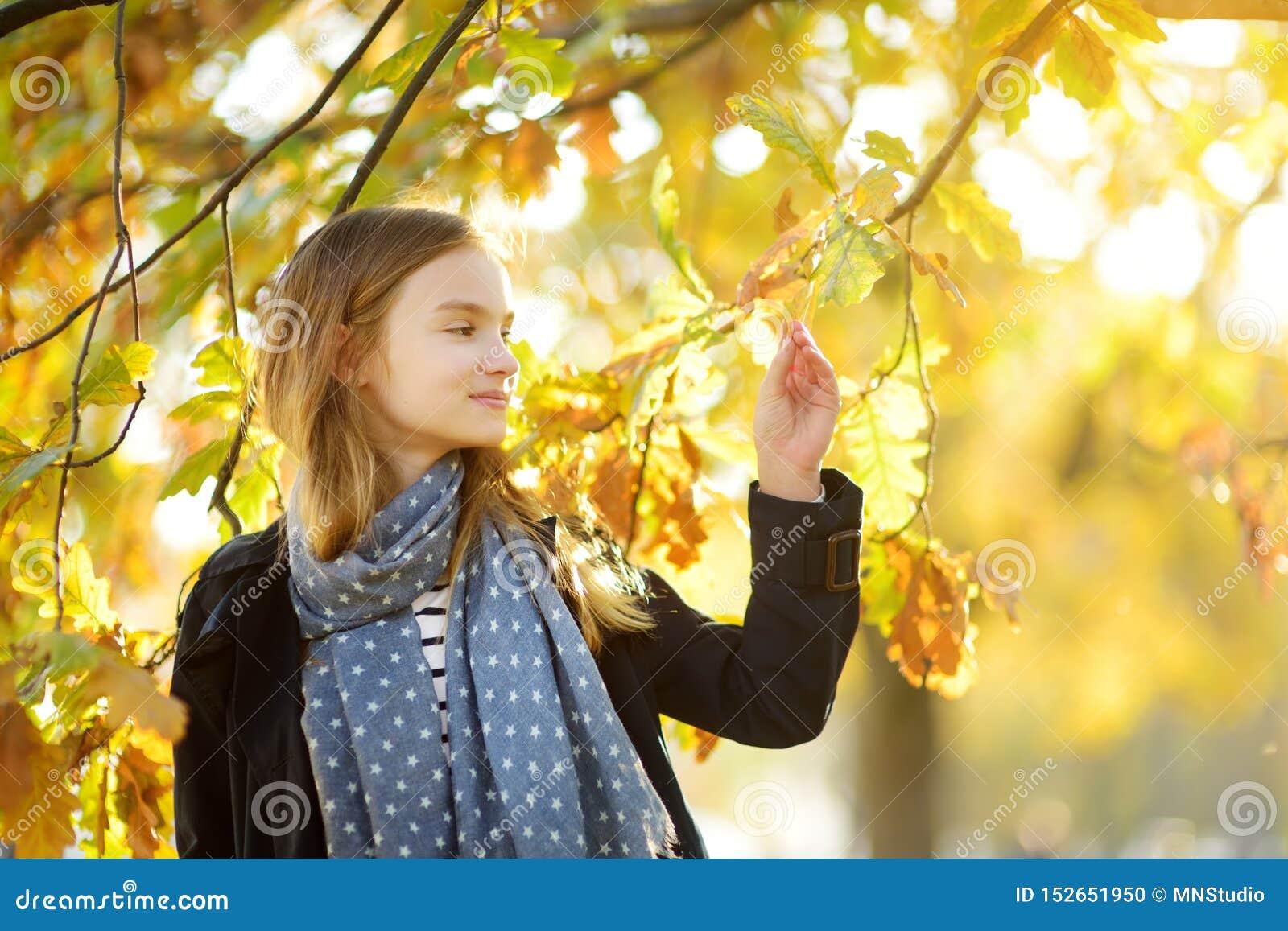 Aanbiddelijk jong meisje die pret op mooie de herfstdag hebben Het gelukkige kind spelen in de herfstpark Jong geitje die geel da