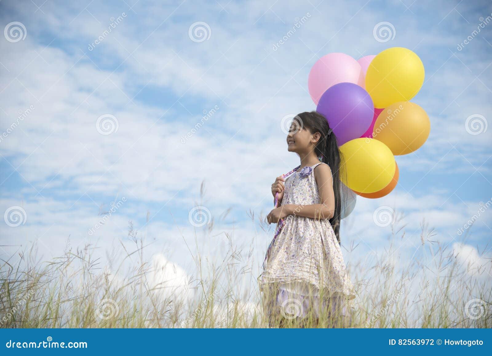 Aanbiddelijk leuk meisje die kleurrijke ballons met de blauwe hemel houden