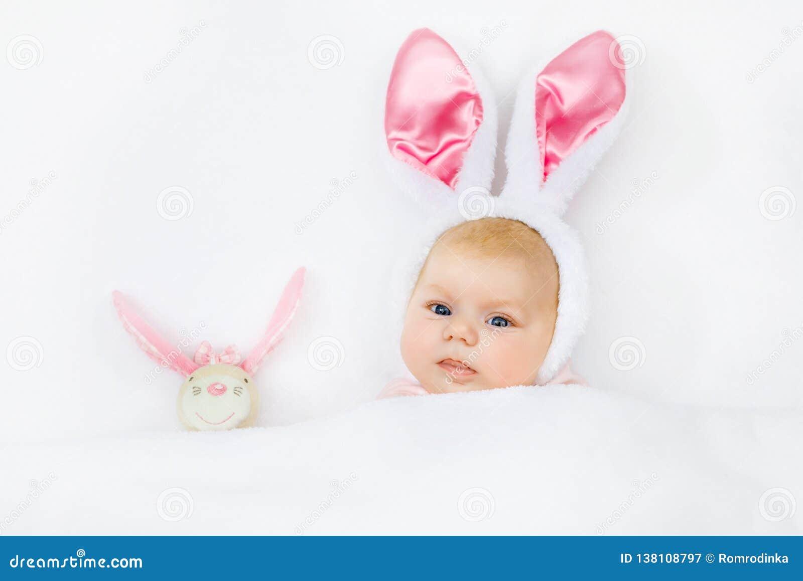 Aanbiddelijk leuk pasgeboren babymeisje in Paashaaskostuum en oren Het mooie kind spelen met het stuk speelgoed van het pluchekon
