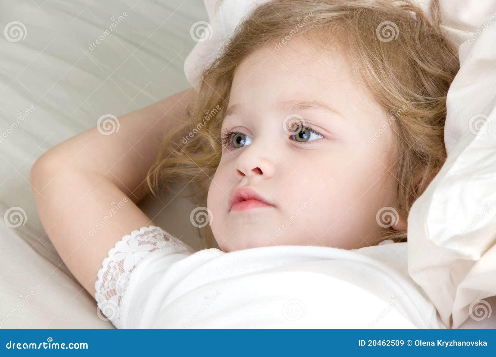 Aanbiddelijk meisje dat in het bed rust