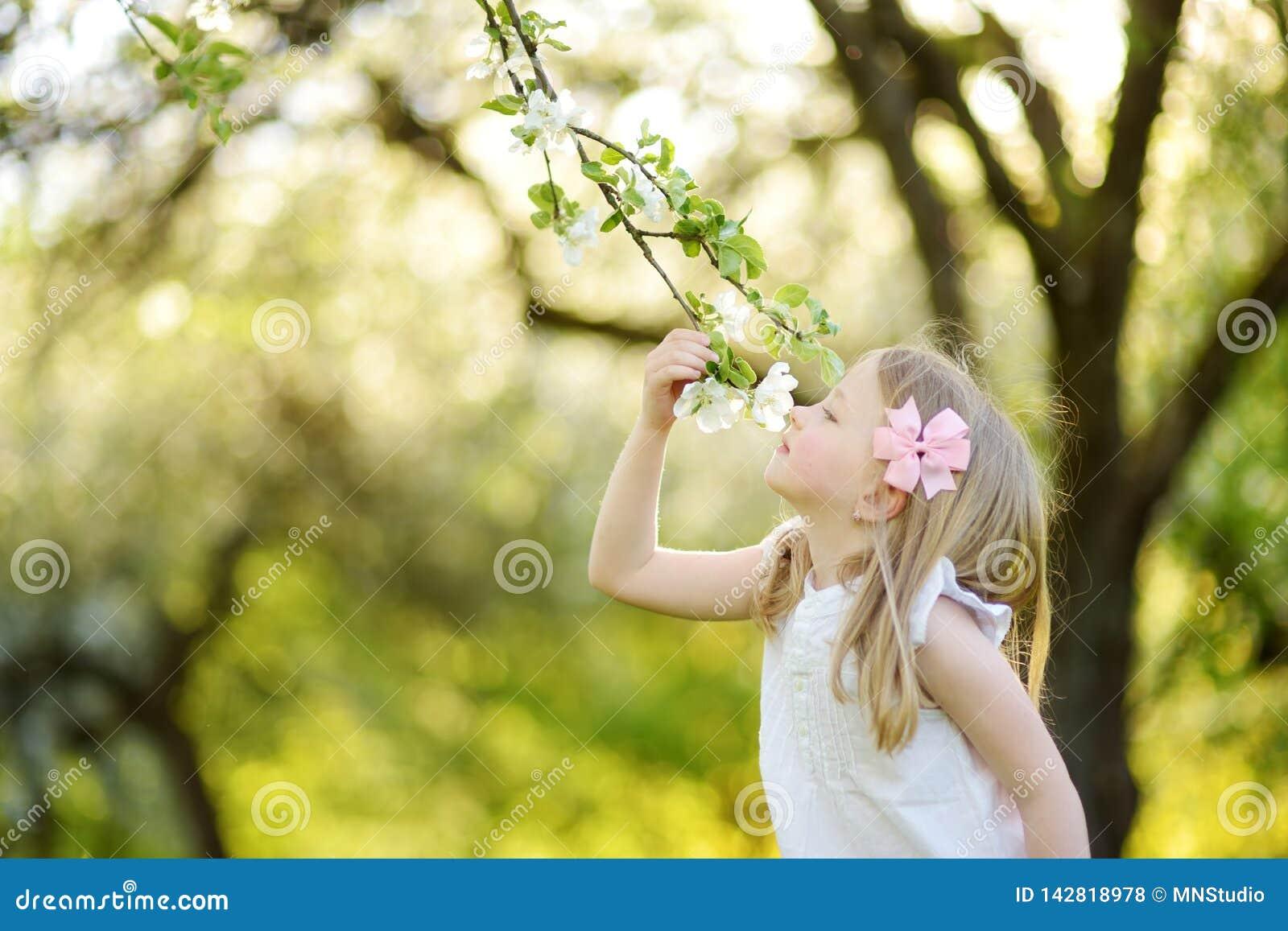 Aanbiddelijk meisje in de bloeiende tuin van de appelboom op mooie de lentedag