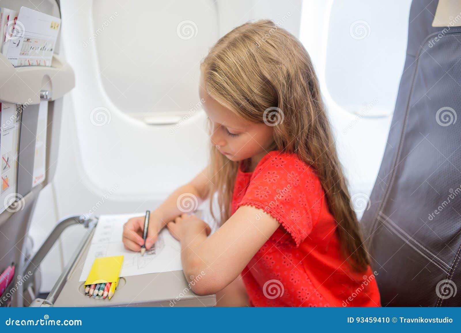 Aanbiddelijk meisje die door een vliegtuig reizen Het beeld van de jong geitjetekening met kleurrijke potloden die dichtbij venst