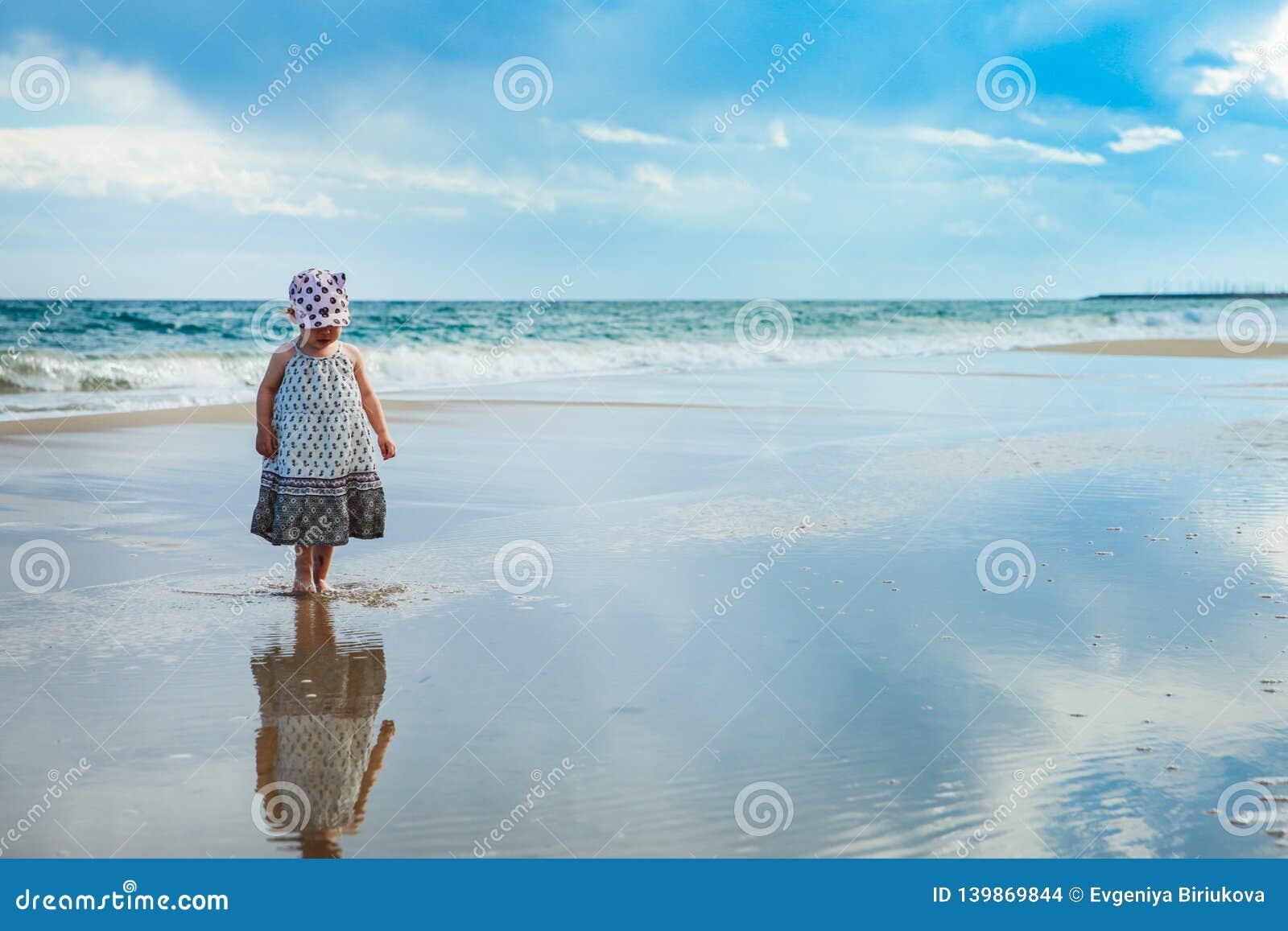 Aanbiddelijk meisje die op het water op het strand lopen