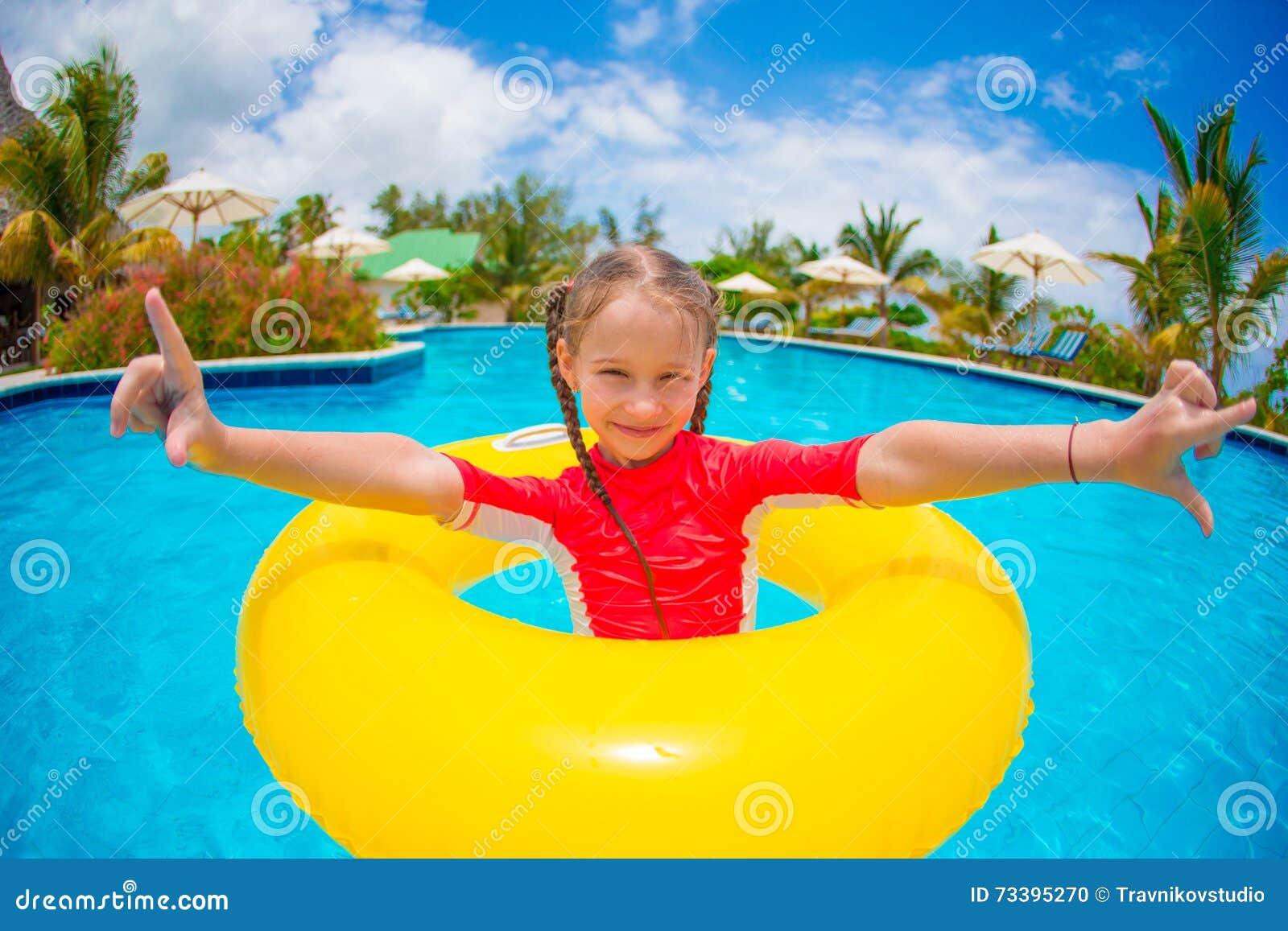 Aanbiddelijk meisje met opblaasbare rubbercirkel tijdens strandvakantie Jong geitje die pret op de zomer actieve vakantie hebben