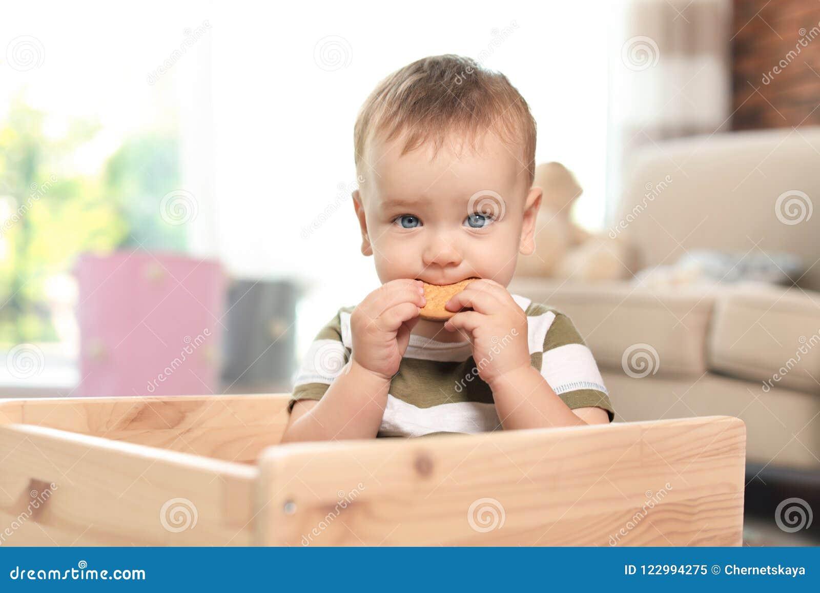 Aanbiddelijk weinig baby die smakelijk koekje eten