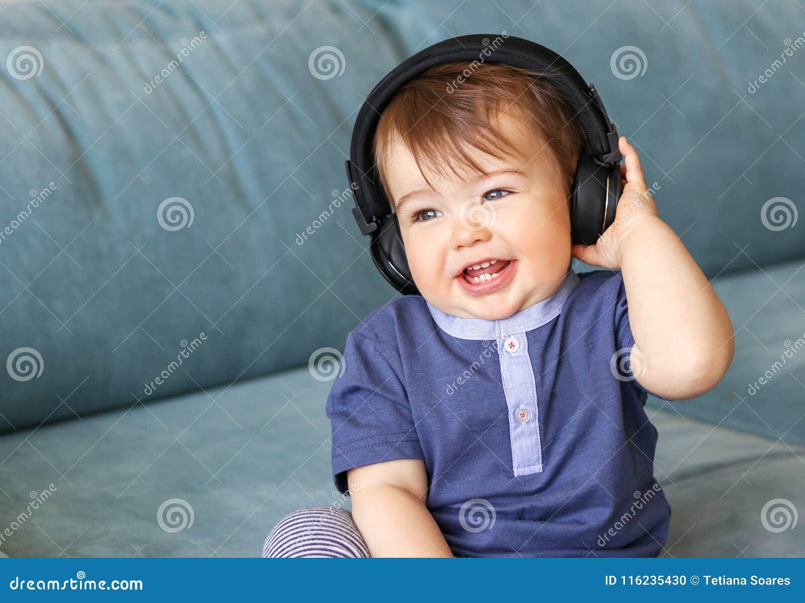 Aanbiddelijk weinig babyjongen die aan muziek in hoofdtelefoons op zijn hoofdzitting op blauwe bank thuis luisteren