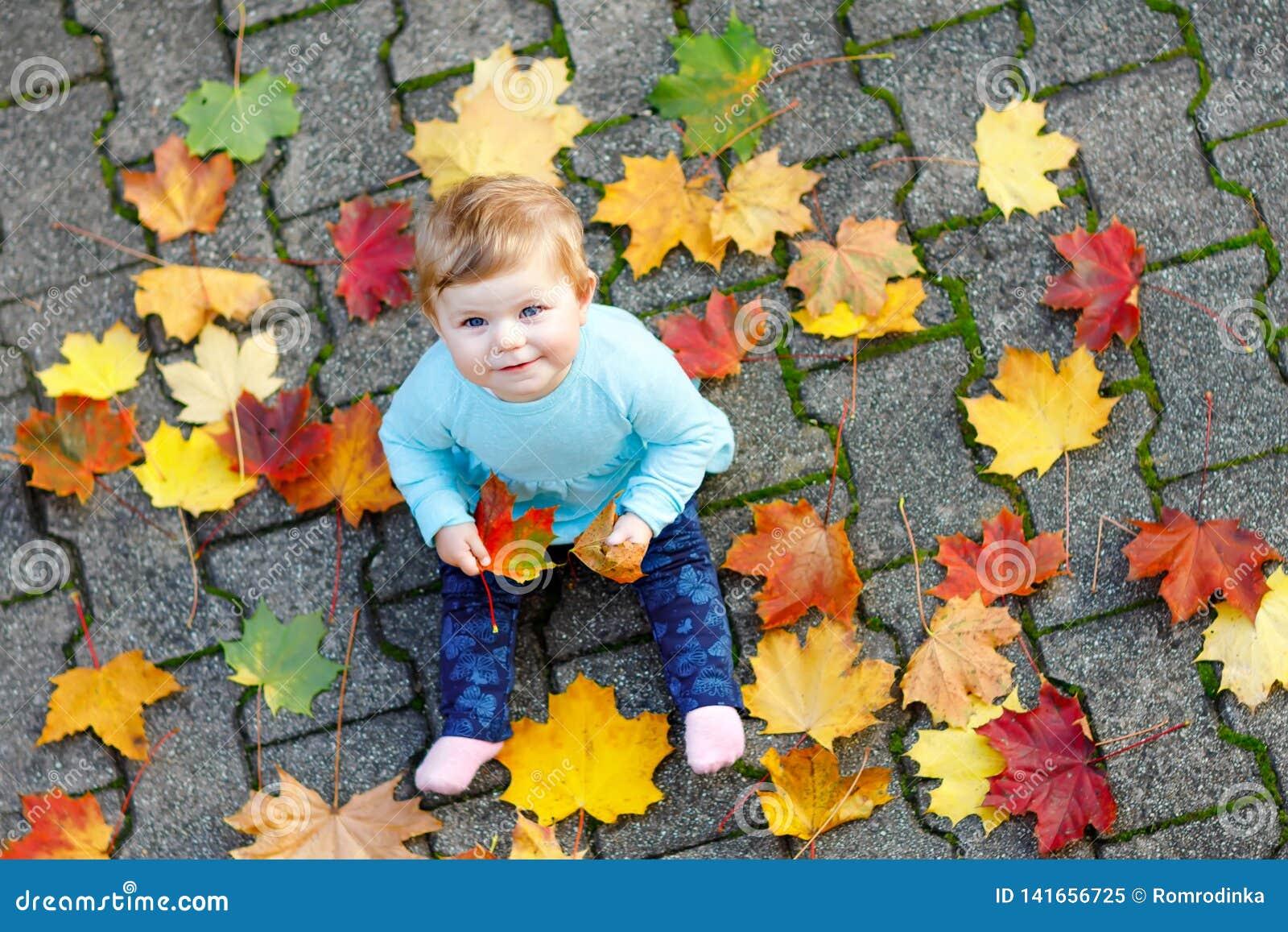 Aanbiddelijk weinig babymeisje in de herfstpark op zonnige warme oktober-dag met eik en esdoornblad Het gebladerte van de daling