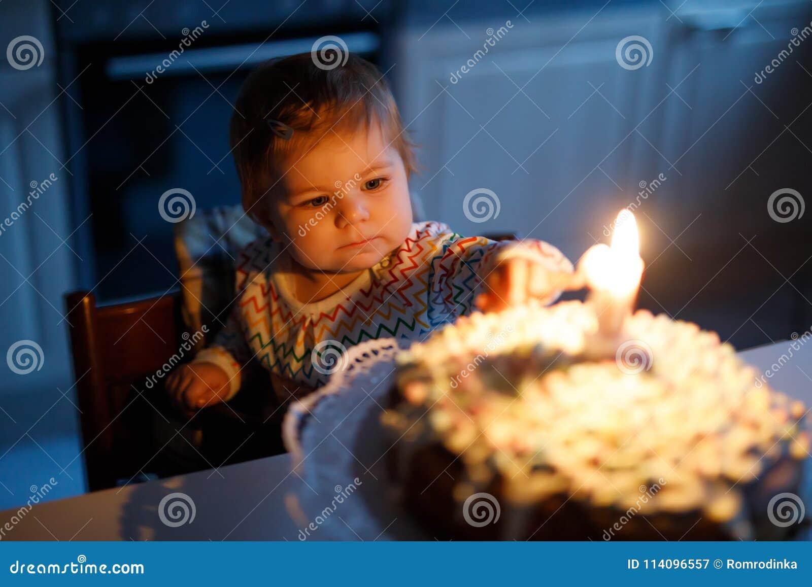 Aanbiddelijk weinig babymeisje het vieren eerste verjaardag Kind die één kaars op eigengemaakte gebakken cake blazen, binnen
