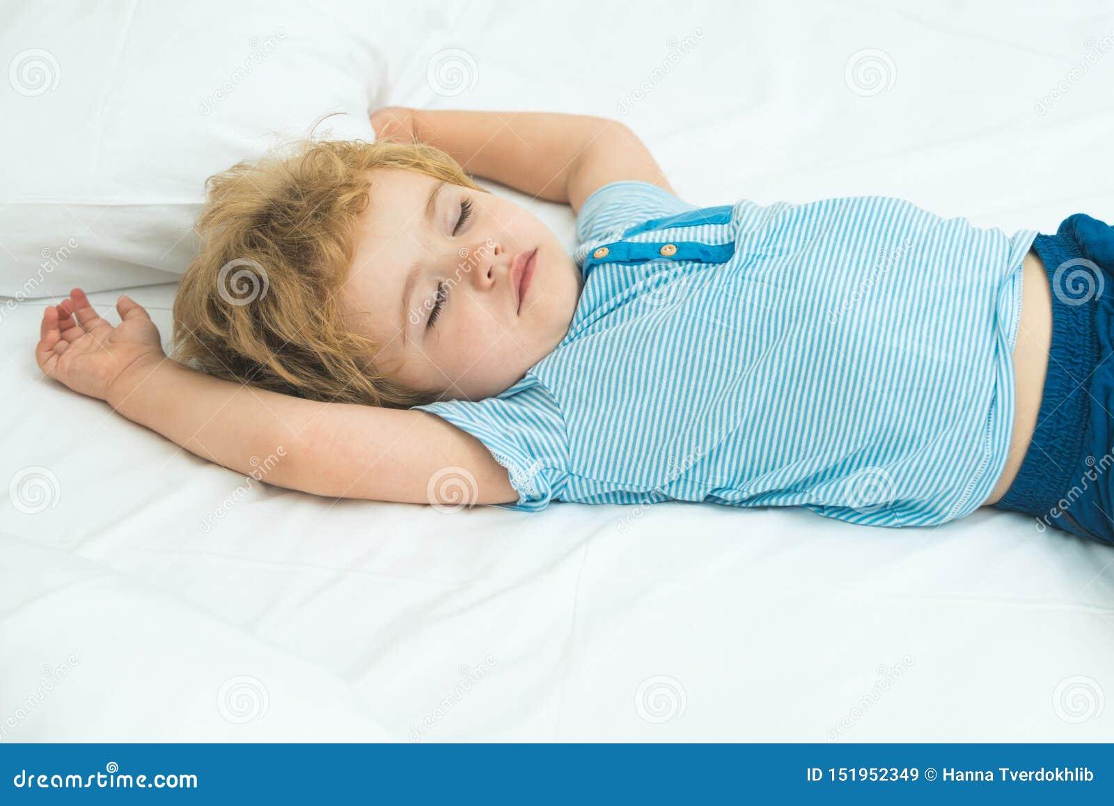 Aanbiddelijk weinig blonde jong geitjejongen in kleren die en in zijn wit bed slapen dromen Gezond kind met zachte slecht, vreedz