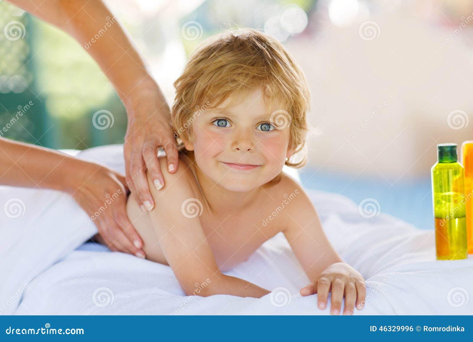 Aanbiddelijk weinig het blonde jong geitje ontspannen in kuuroord met het hebben van massage