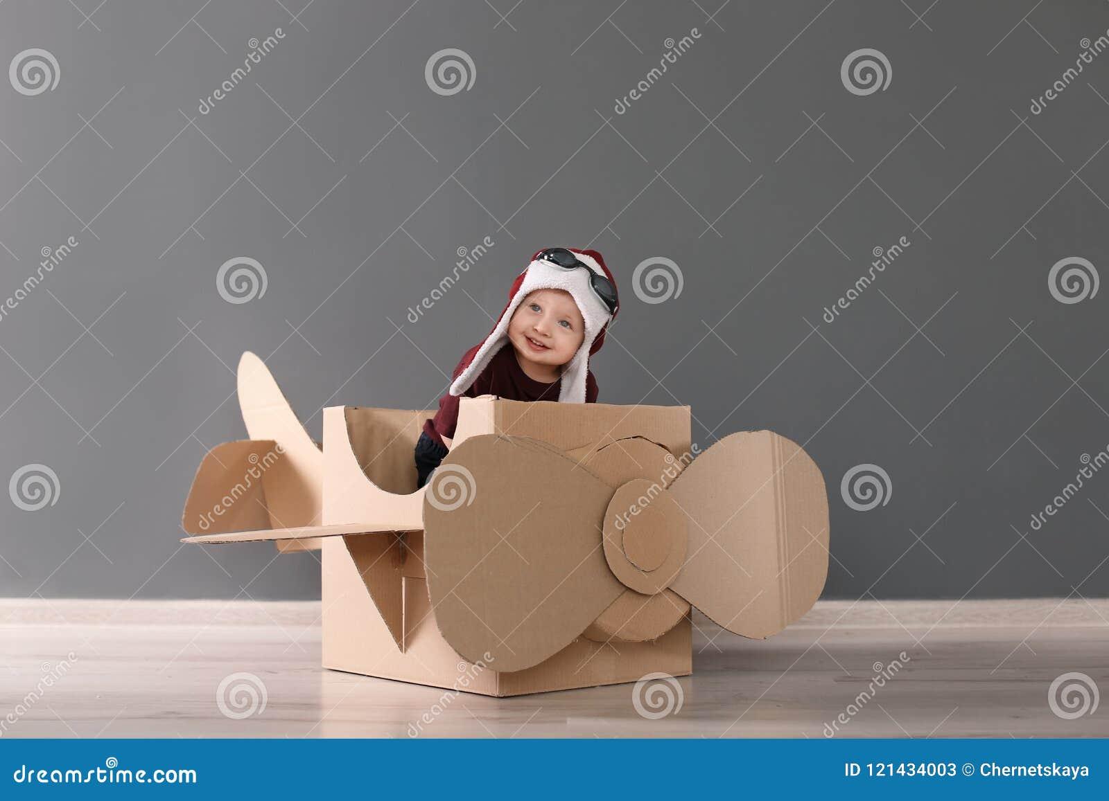 Aanbiddelijk weinig kind die met kartonvliegtuig spelen