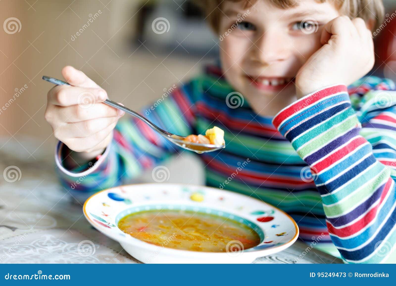 Aanbiddelijk weinig schooljongen die groentesoep eten binnen