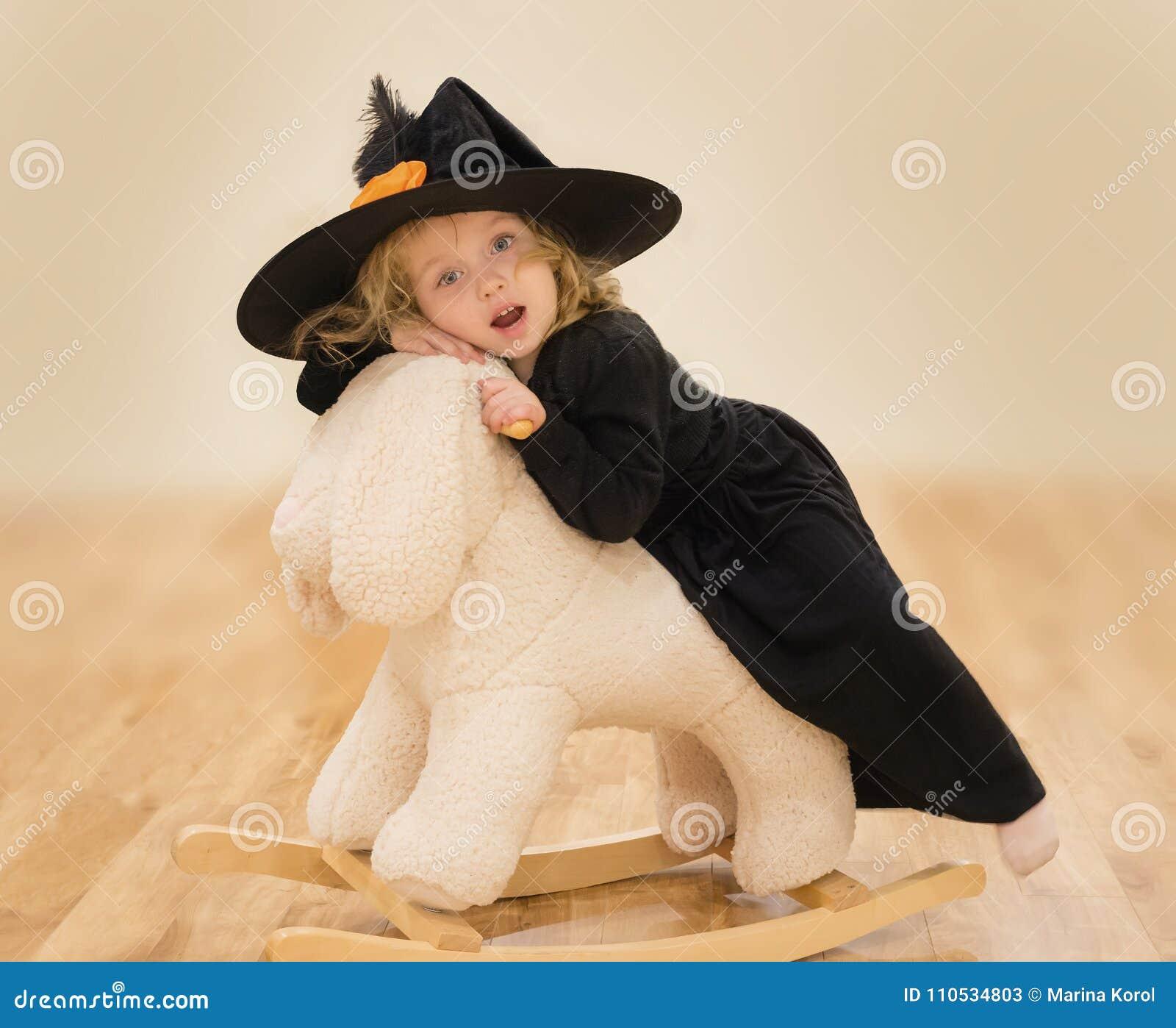 Aanbiddelijk zit weinig Kaukasisch meisje op pluizig konijntjesstuk speelgoed Zij is in zwarte kleding en grote zwarte hoed