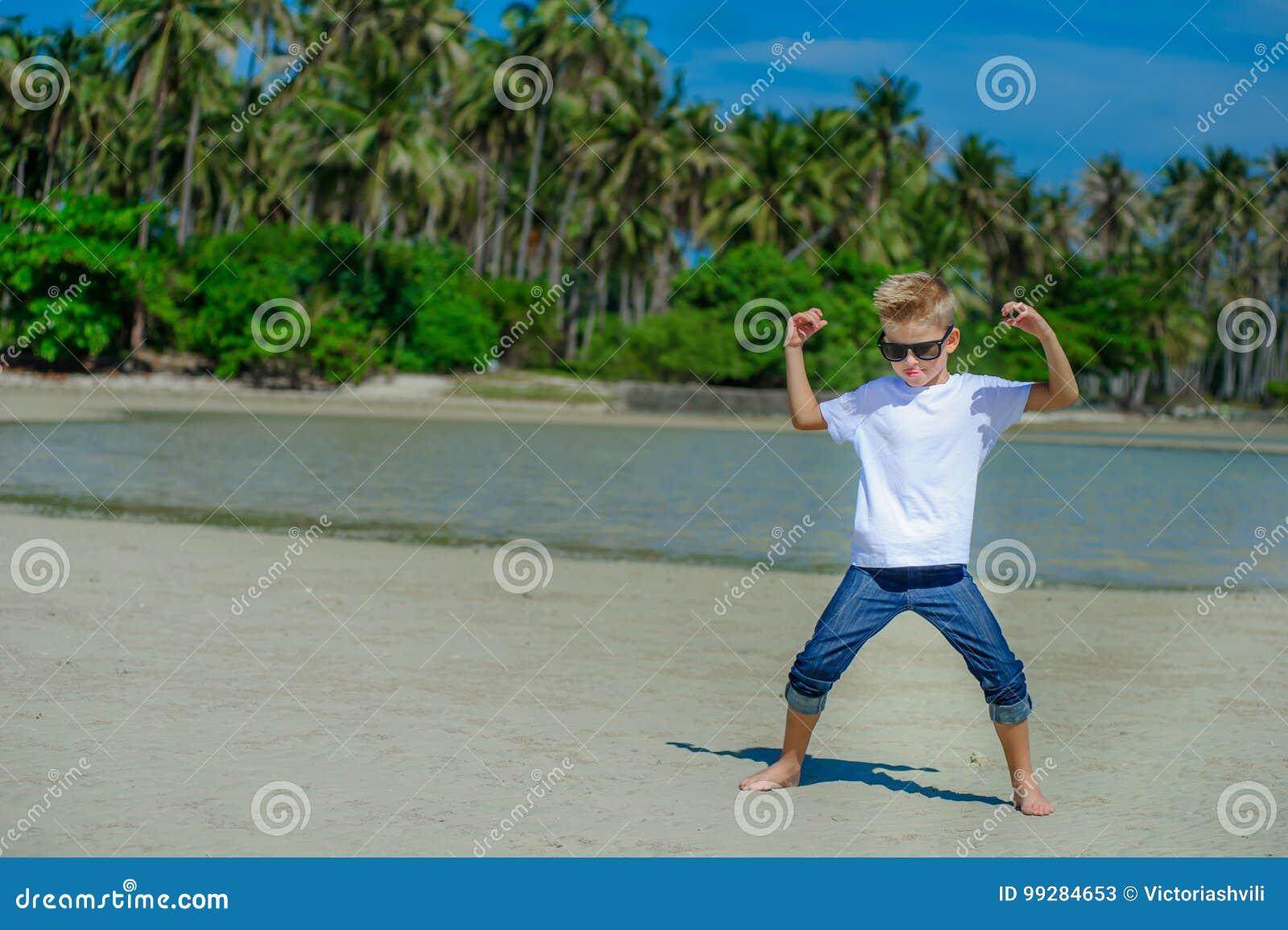 Aanbiddelijke jongen die pret op het tropische strand hebben Witte t-shirt, donkere broeken en zonnebril Blootvoets op wit zand