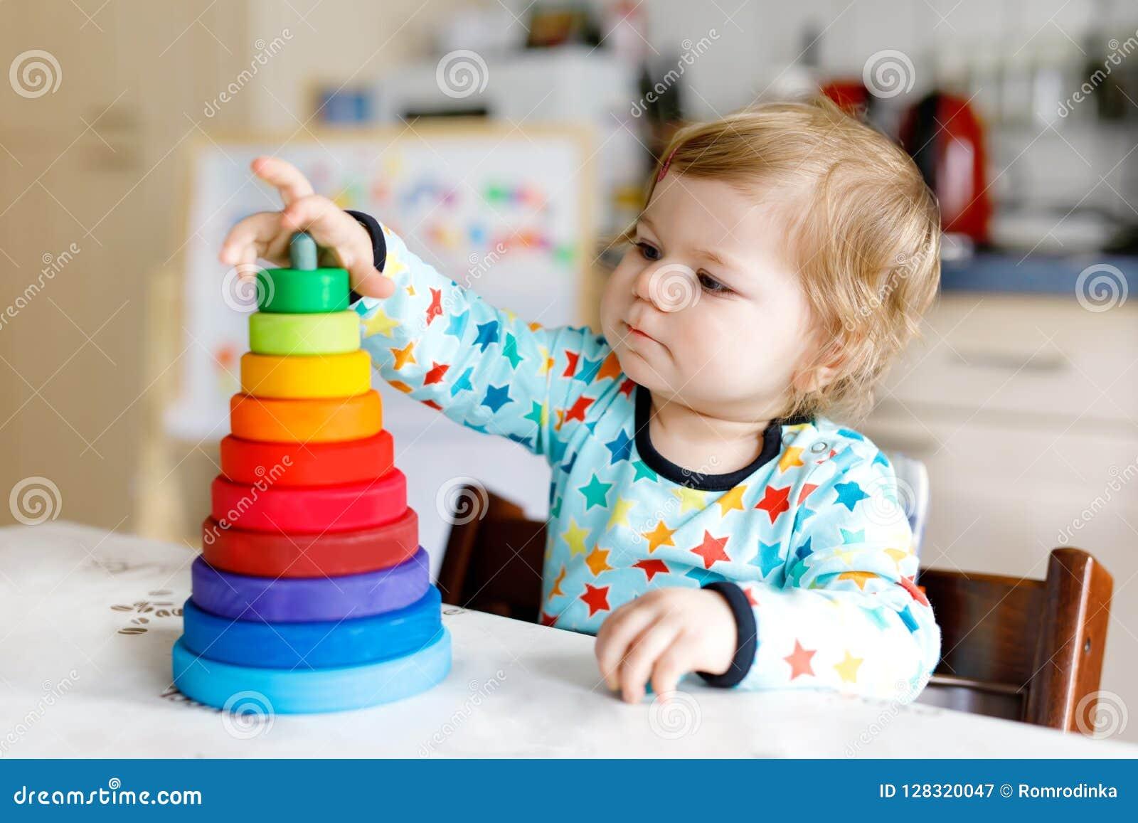 Aanbiddelijke leuk mooi weinig babymeisje die met onderwijs houten regenboogstuk speelgoed piramide spelen