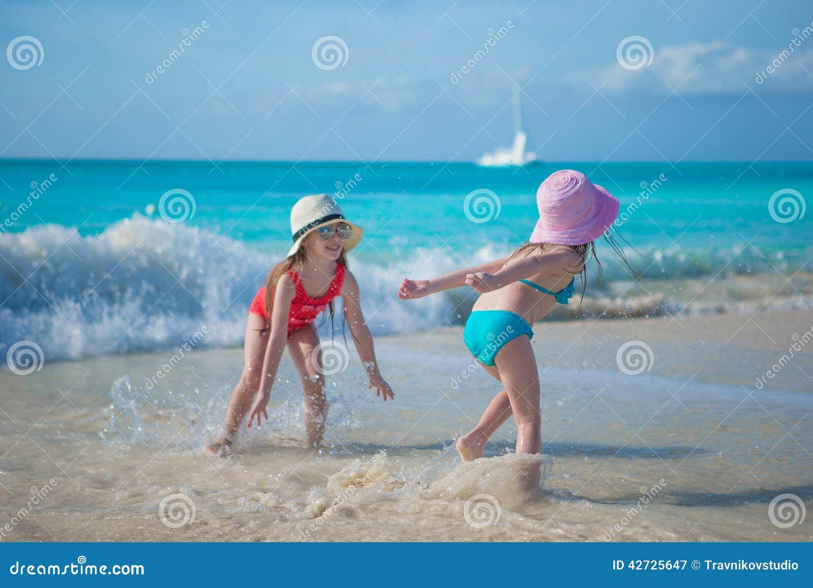 Aanbiddelijke meisjes die in ondiep water spelen bij