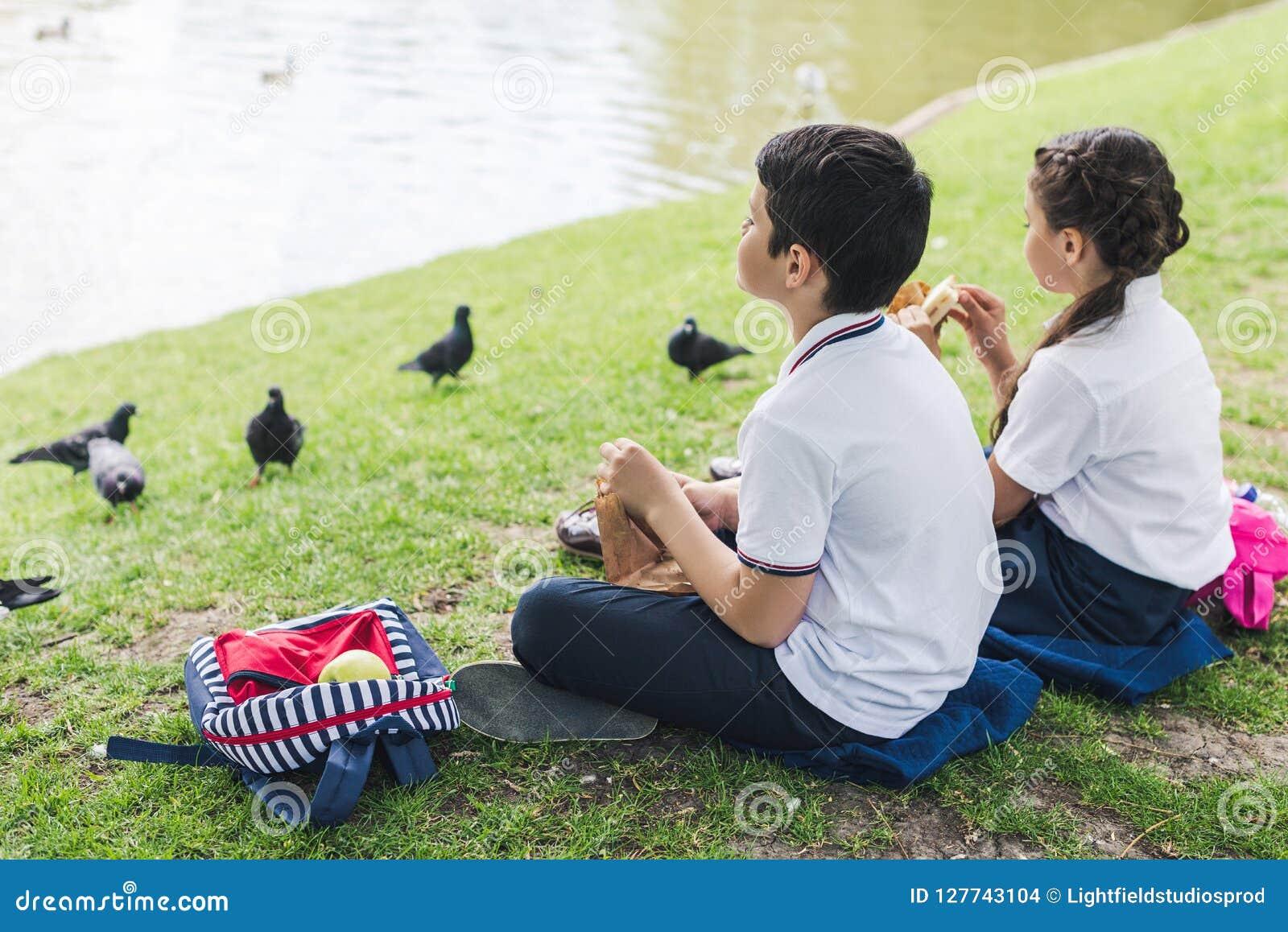 Aanbiddelijke schoolkinderen die op gras zitten