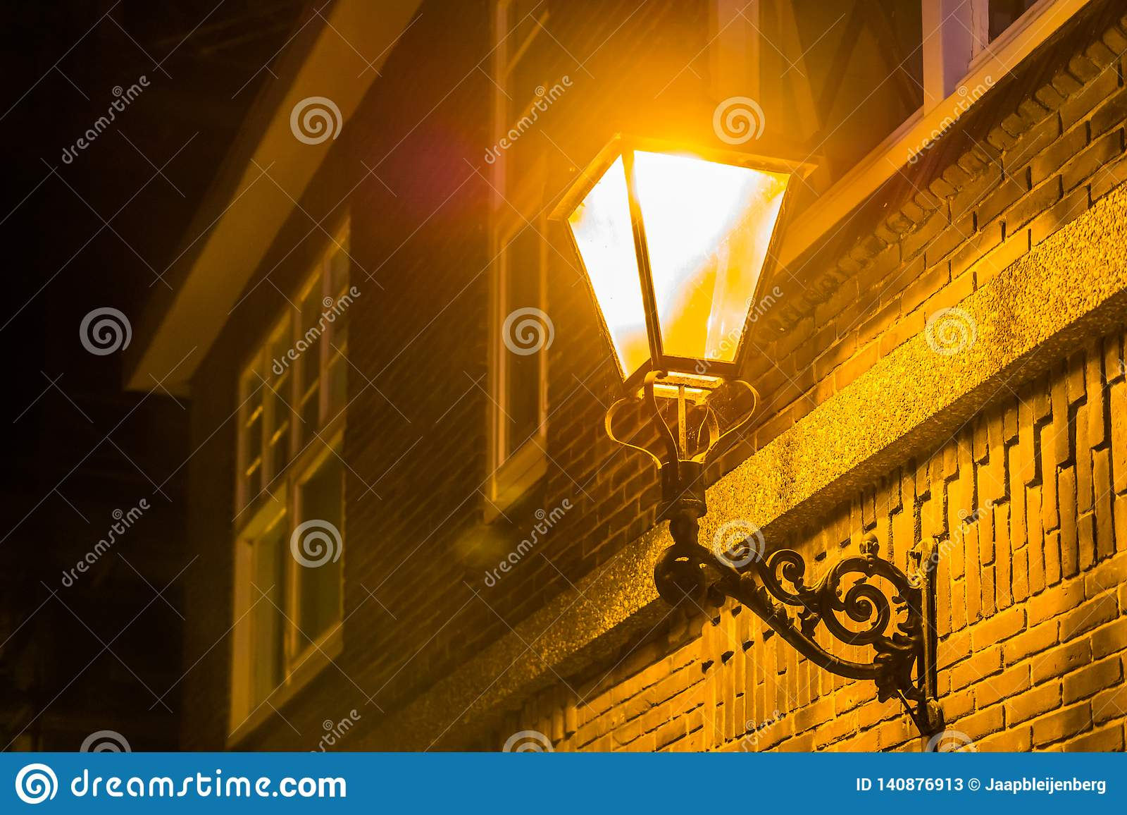 Aangestoken straatlantaarn op de muur van een huis bij nacht, stadslandschap in de avond, uitstekende decoratie