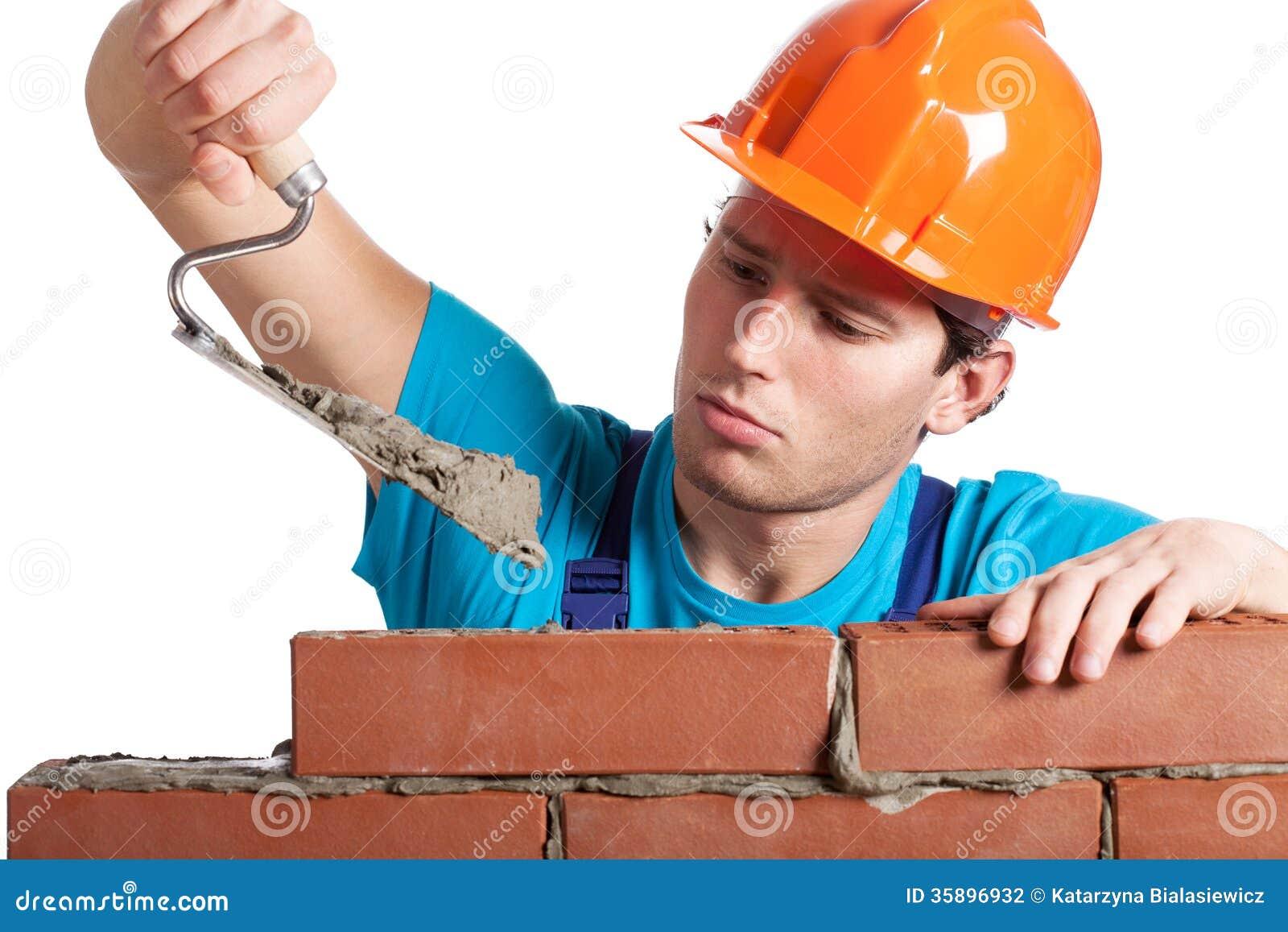 Aannemer met stopverfmes de bouwmuur