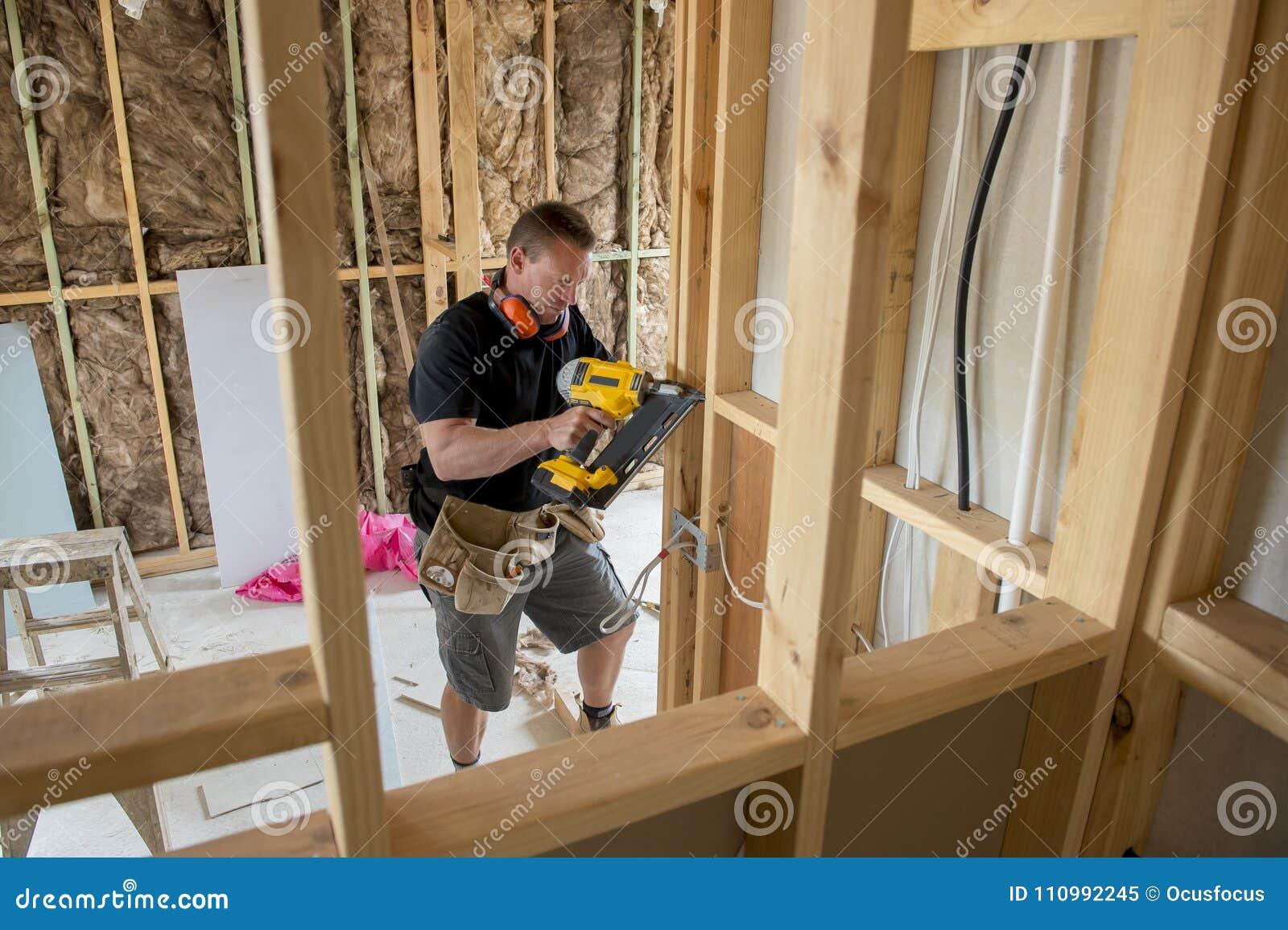 Aantrekkelijk en zeker van de aannemerstimmerman of bouwer mensen werkend hout met elektrische boor bij industriële bouwwerf