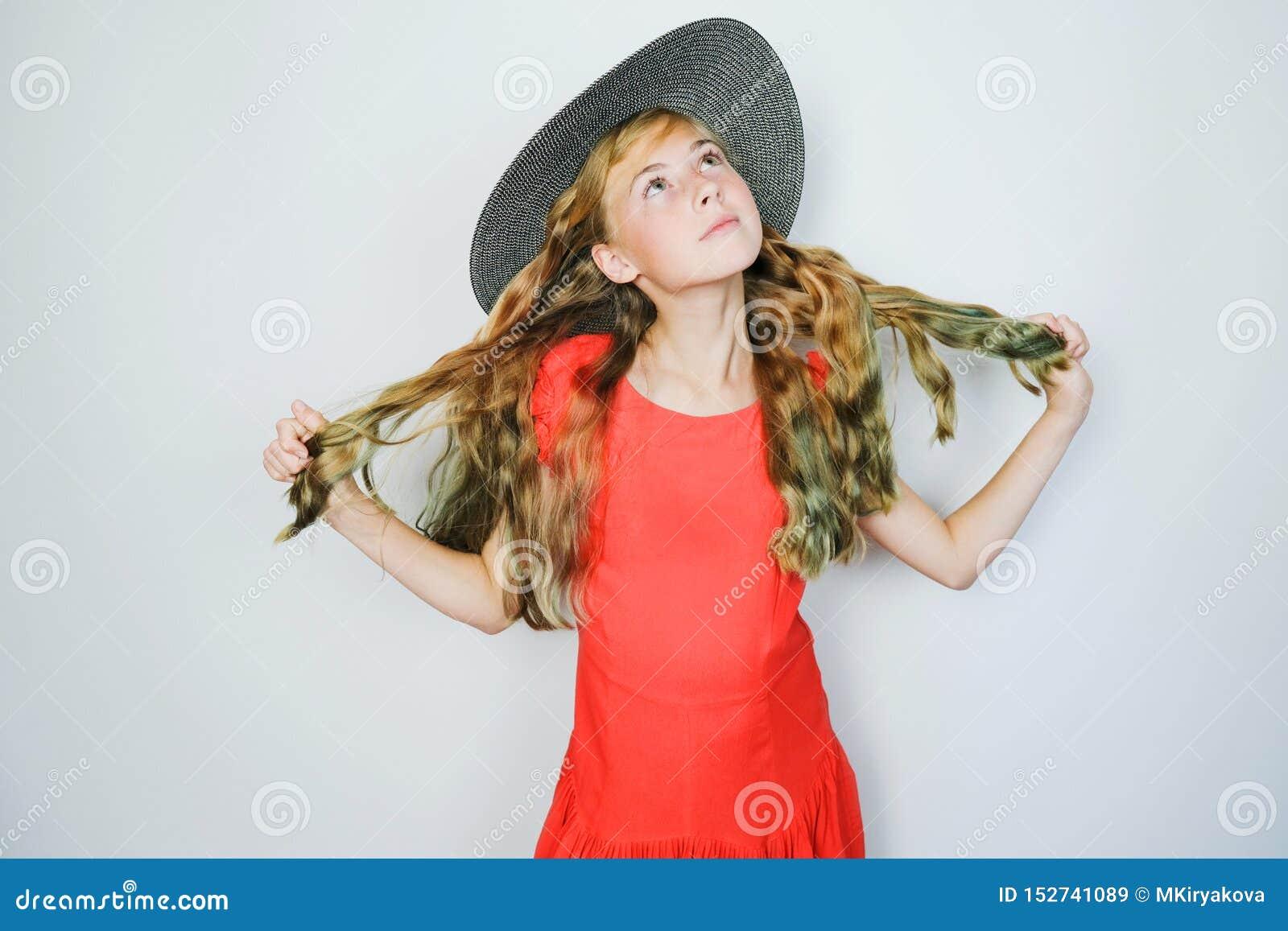 Aantrekkelijk Kaukasisch tienermeisje in rode kleding en hoed die omhoog dreamily eruit zien