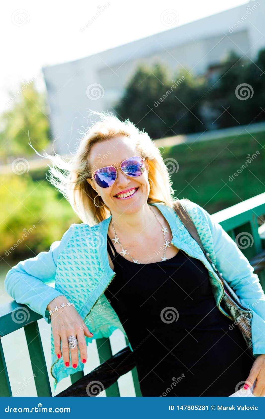 Aantrekkelijke blondevrouwen die op brug stellen