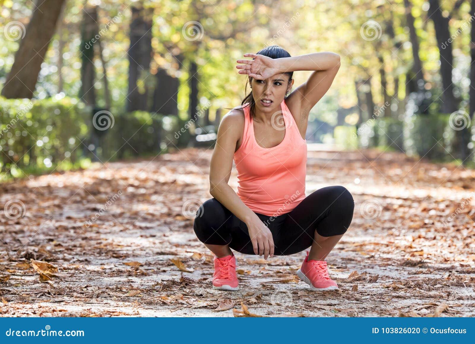 Aantrekkelijke die sportvrouw in agentsportkleding ademhaling hijgend en nemend een onderbreking en uitgeput na het runnen van tr