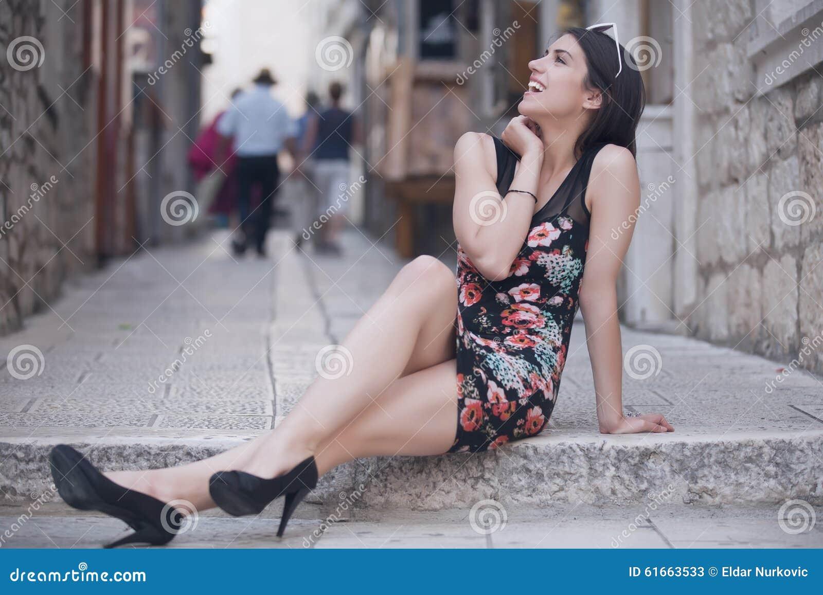 Aantrekkelijke donkerbruine elegante vrouw die pret hebben die van zomer, lachen en glimlachen de gelukkig tijdens de vakantierei