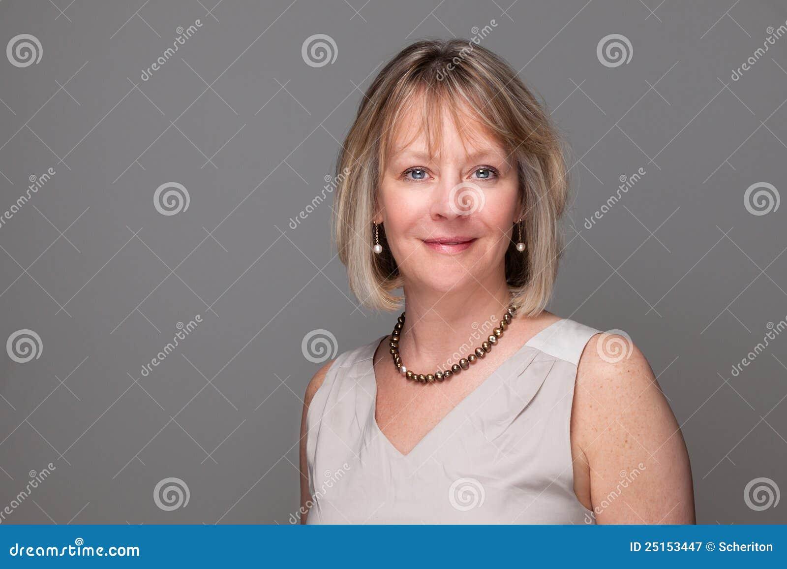 Aantrekkelijke Glimlachende Elegante Vrouw op Grijs