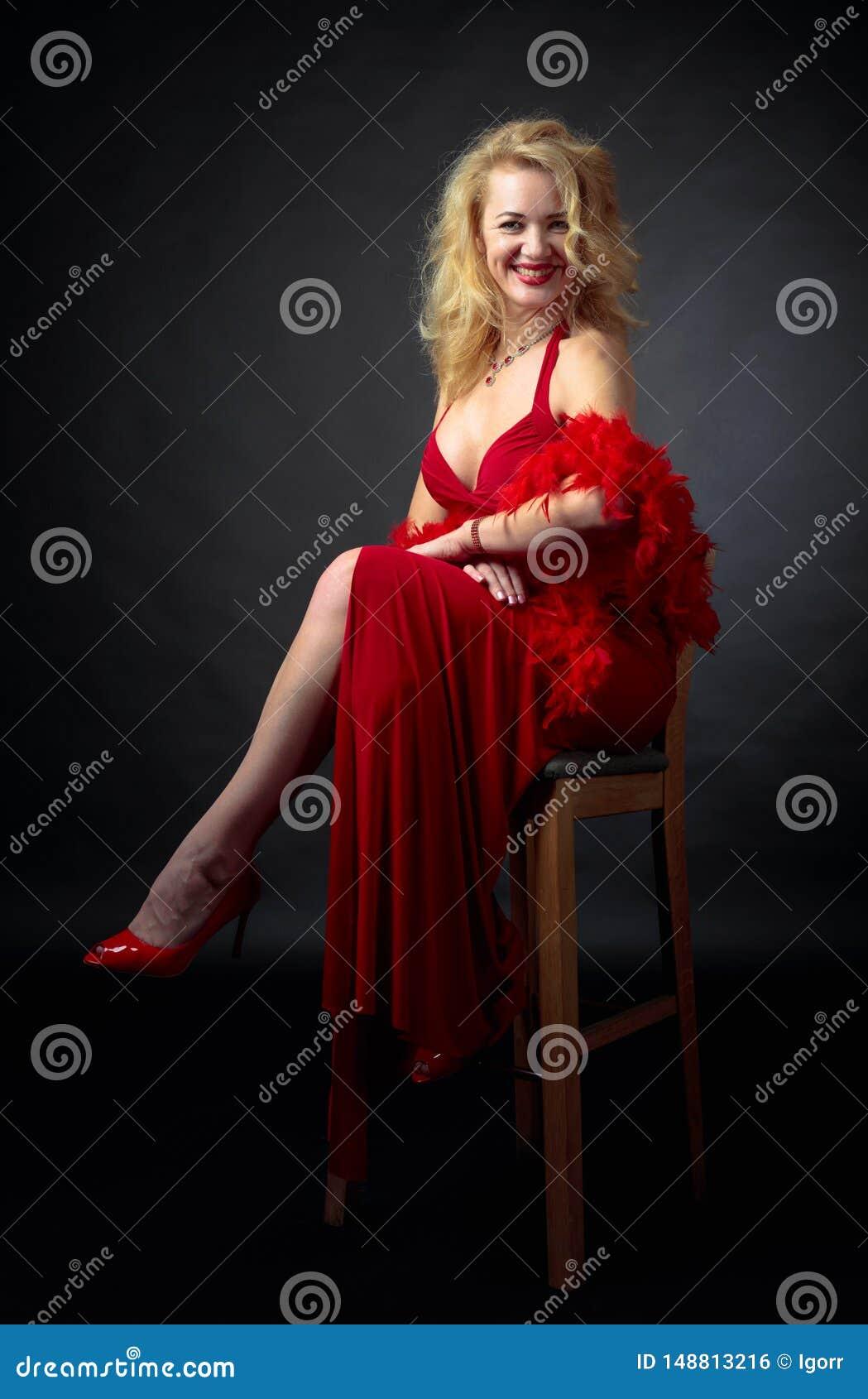 Aantrekkelijke glimlachende rijpe vrouw in rode avondjurk met pluizige veerboa