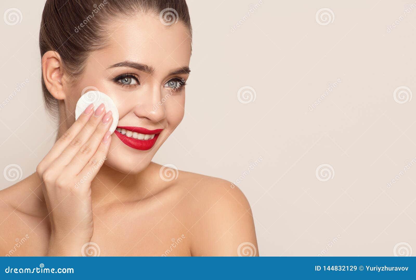 Aantrekkelijke glimlachende vrouw die katoenen stootkussen gebruiken
