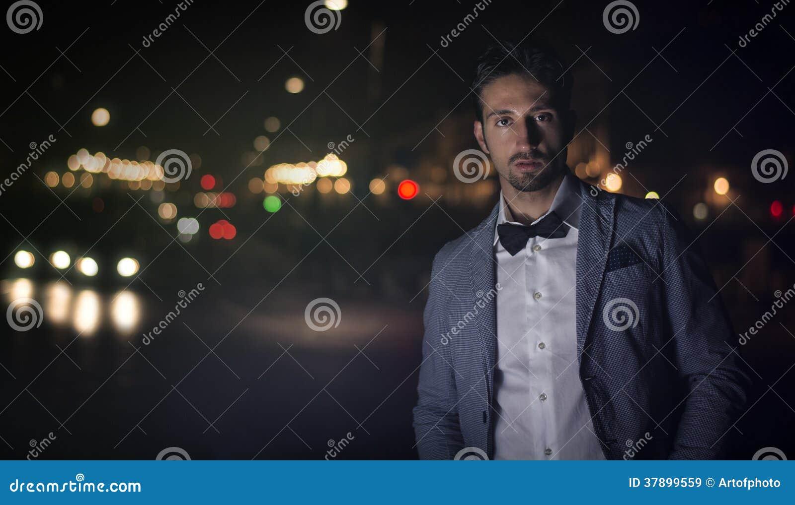 Aantrekkelijke jonge mens bij nacht met stadslichten achter hem
