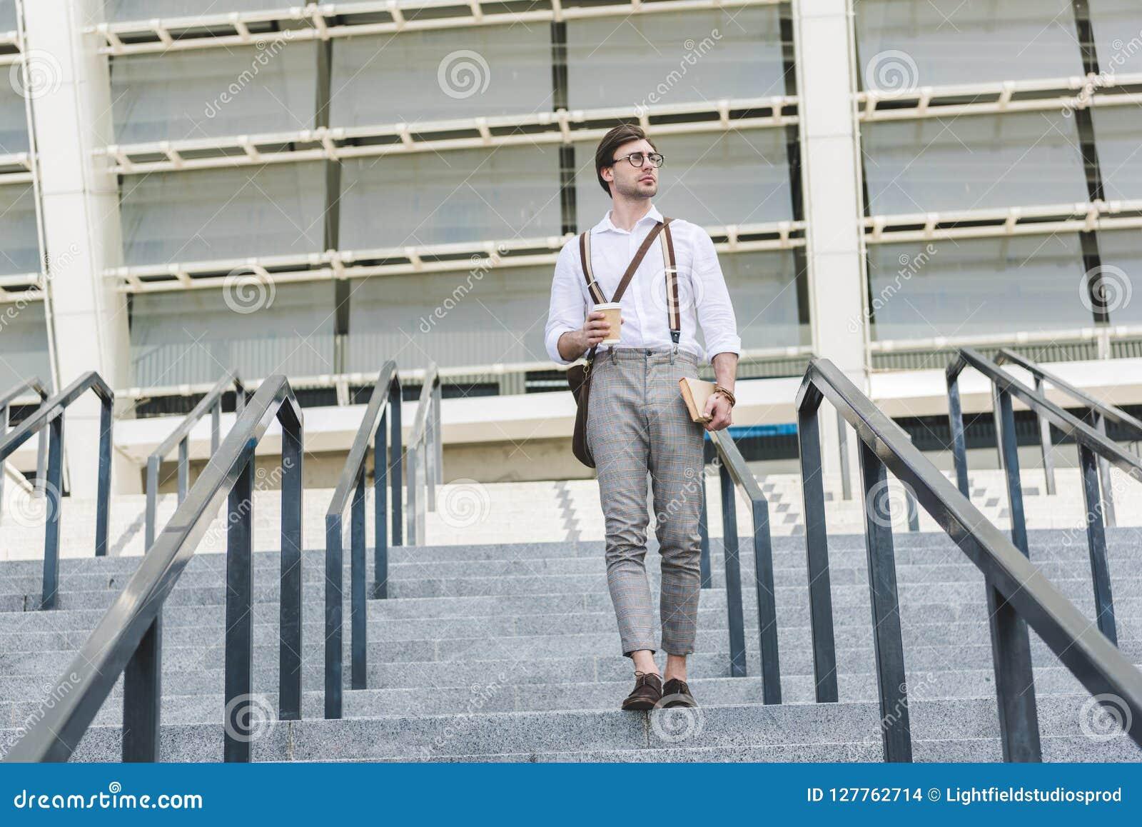 Aantrekkelijke jonge mens die onderaan treden voor stadion met boek en koffie lopen