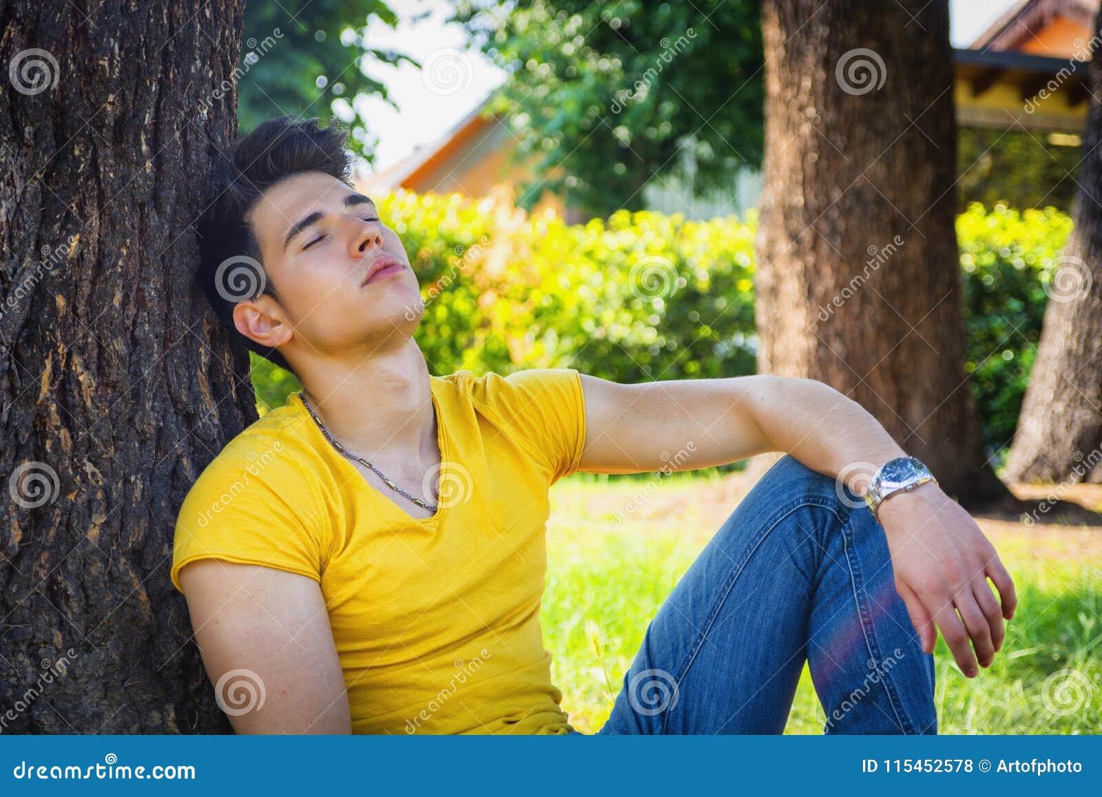 Aantrekkelijke jonge mens in park die tegen boom rusten