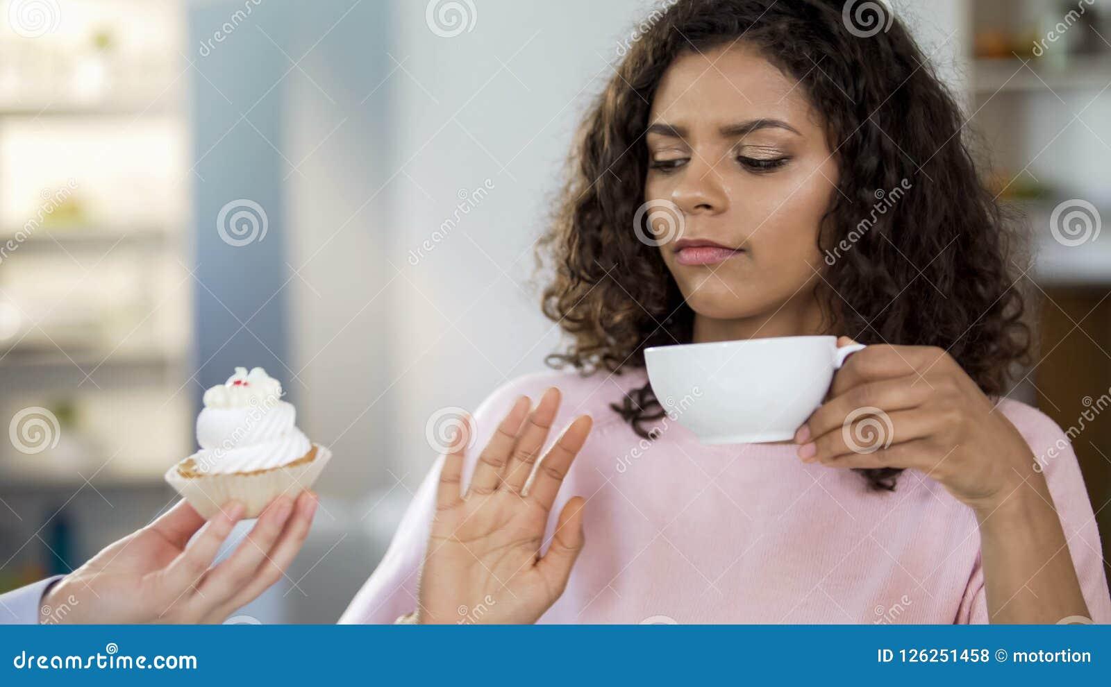 Aantrekkelijke jonge vrouw het drinken thee, die nr aan room-cake, het gezonde op dieet zijn zeggen