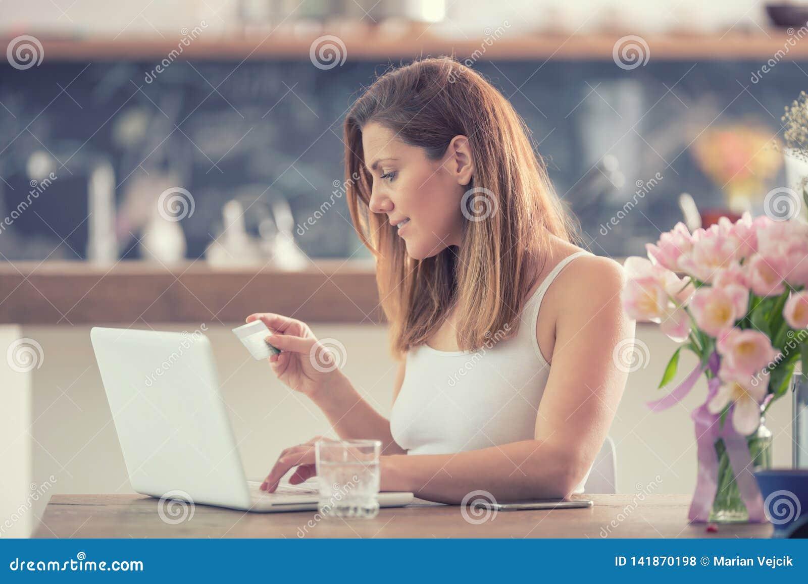 Aantrekkelijke jonge vrouw online het winkelen gebruikende computer en creditcard in huiskeuken