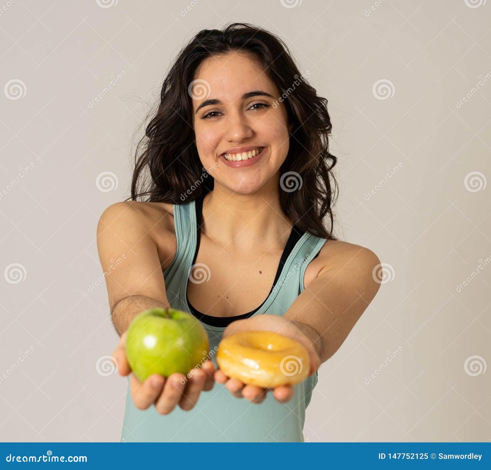 Aantrekkelijke jonge vrouw op een dieet die tussen een appel en een doughnut beslissen