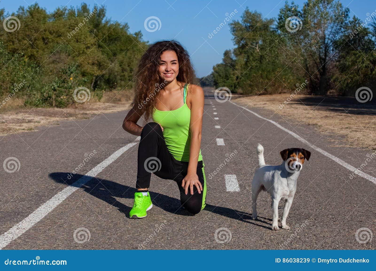 Aantrekkelijke krullende meisjesatleet die ochtendoefeningen met haar hond op de straat doen