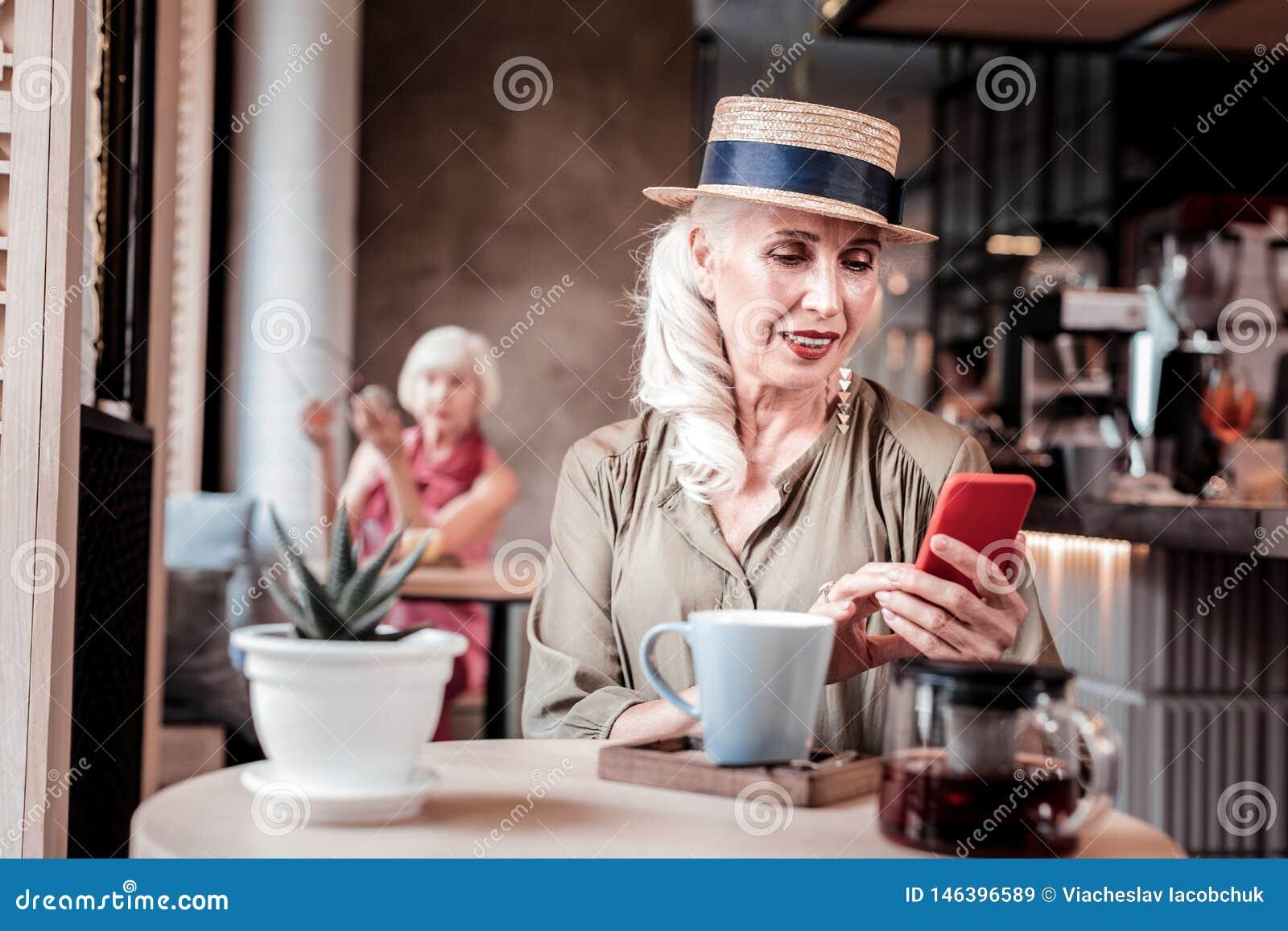 Aantrekkelijke langharige oude vrouw die in strohoed haar smartphone waarnemen