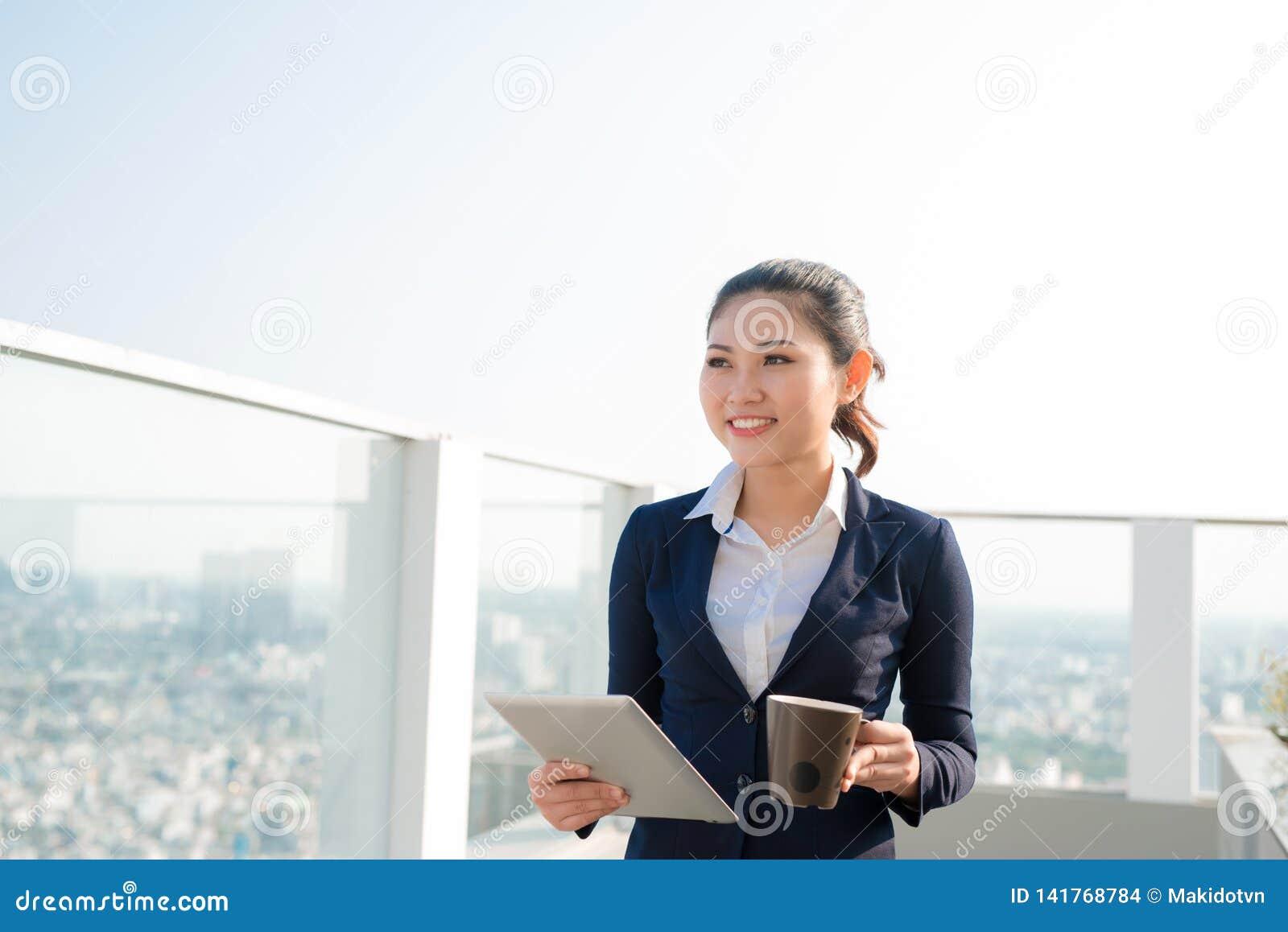 Aantrekkelijke onderneemster die een koffie drinken en een digitale tablet status openlucht en het kijken gebruiken de stad