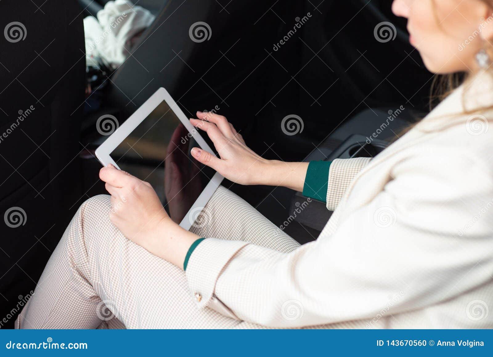 Aantrekkelijke uitvoerende vrouwelijke manager die met een tablet in een achterbank van een auto werken