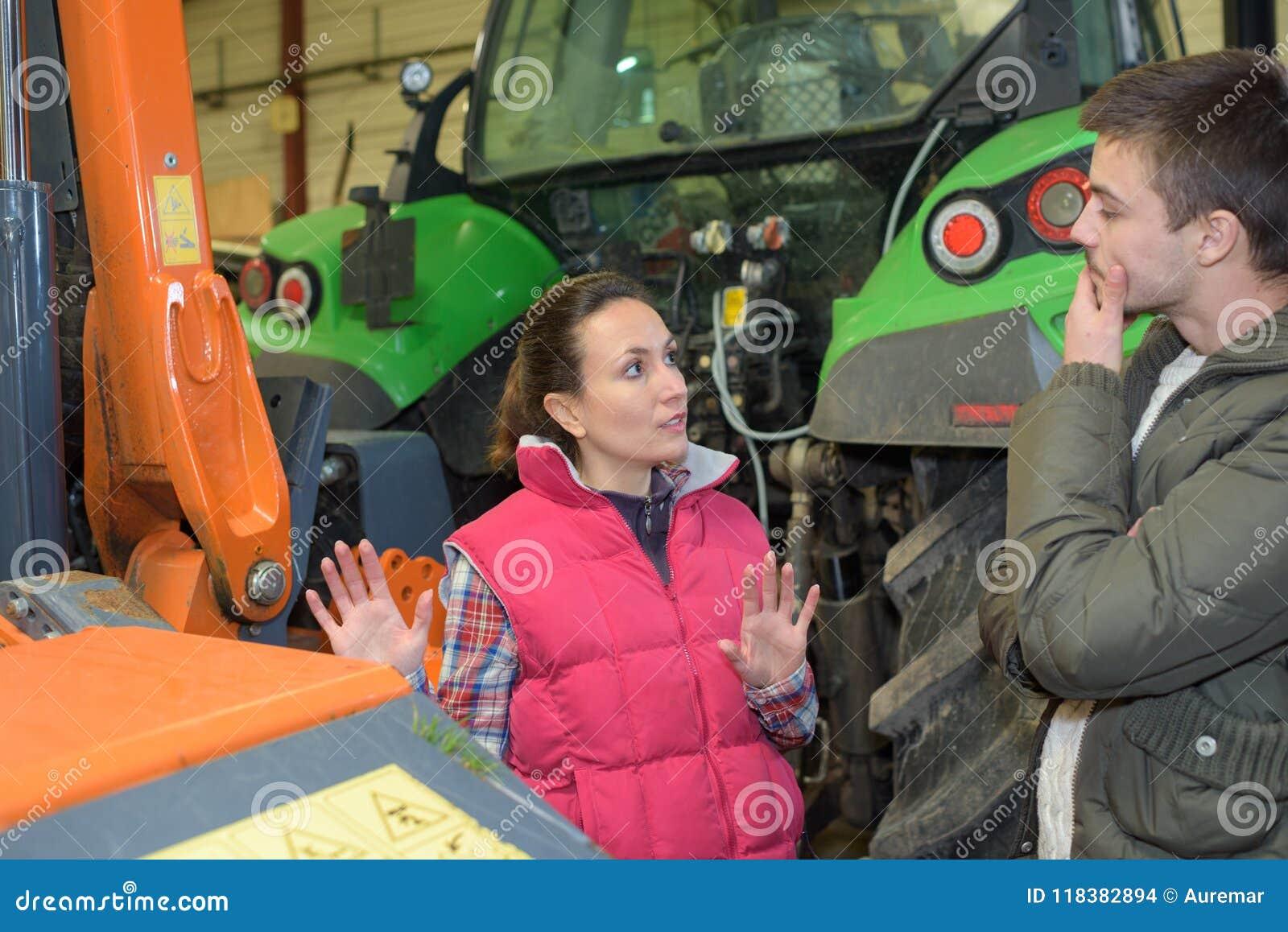 Aantrekkelijke vrouw die gloednieuwe tractor verkopen aan beginnerslandbouwer