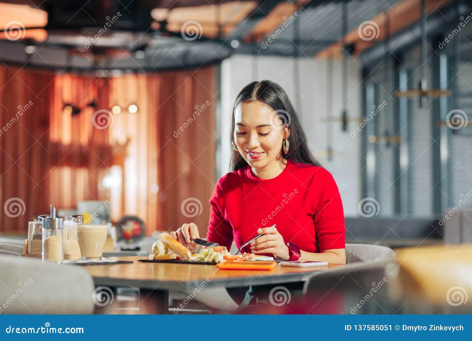 Aantrekkelijke vrouw die met lang donker haar lunch in restaurant eten
