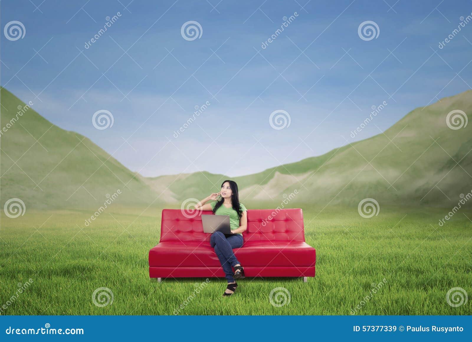 Aantrekkelijke vrouw die op rode bank denken openlucht