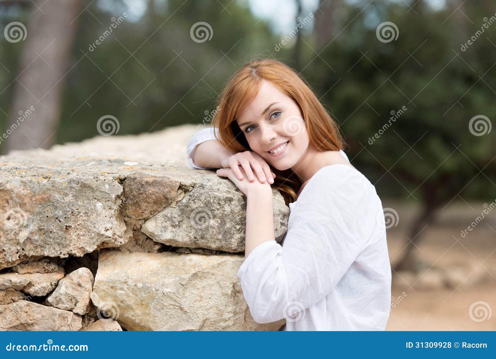 Aantrekkelijke vrouw die tegen een steenmuur leunen