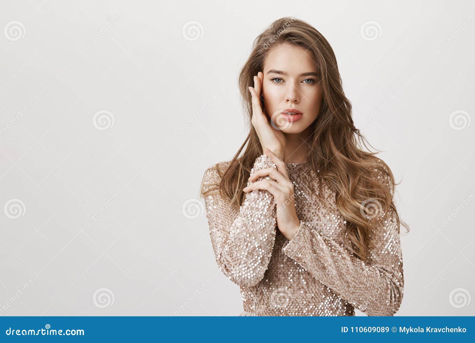 Aantrekkelijke vrouwelijke vrouw met mooi lang haar die zich in modieuze avondjurk, zacht wat betreft gezicht bevinden alsof