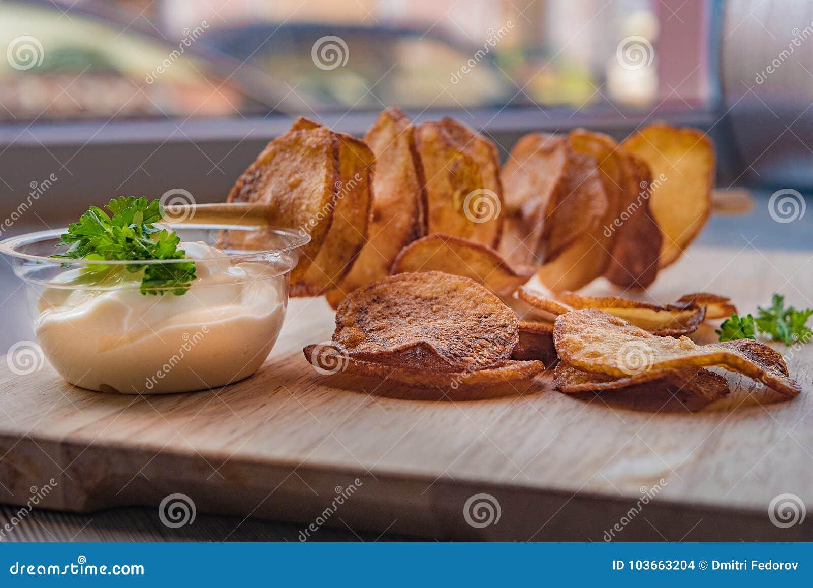 Aardappels in plakken, op een stok worden gesneden die