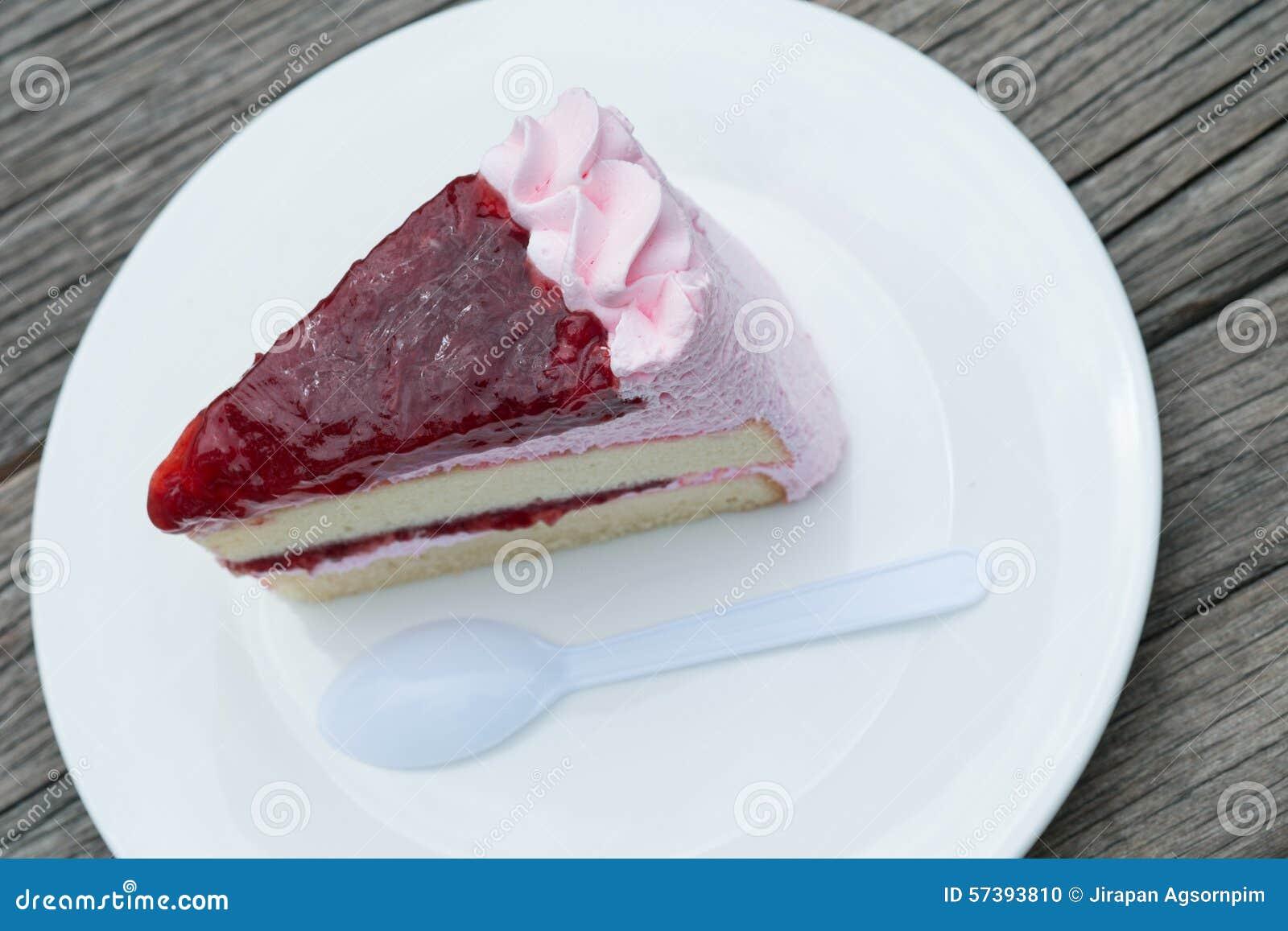 Aardbeicake op witte plaat met plastic lepel