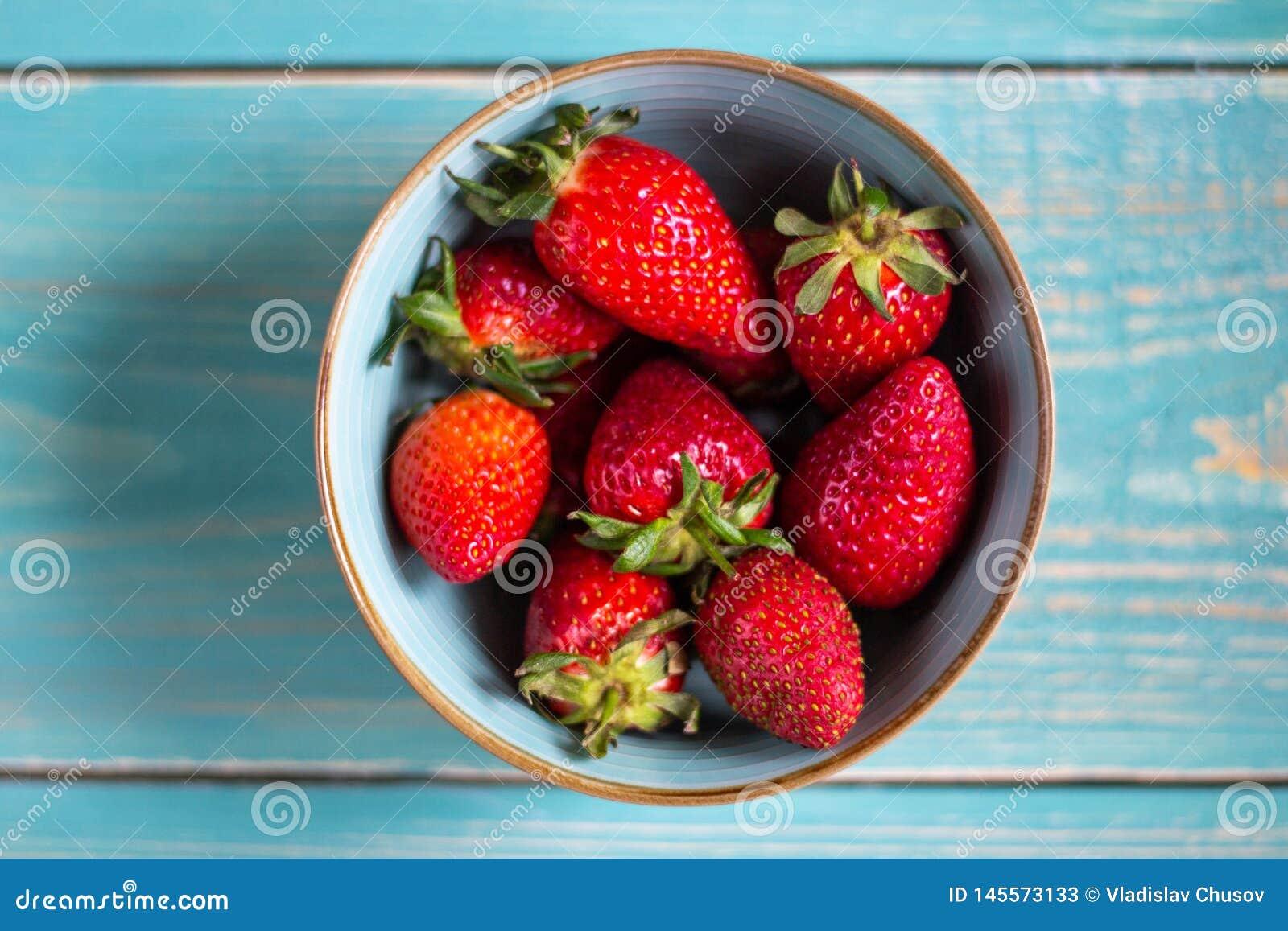Aardbeien in een kom op een houten achtergrond Het gezonde Eten