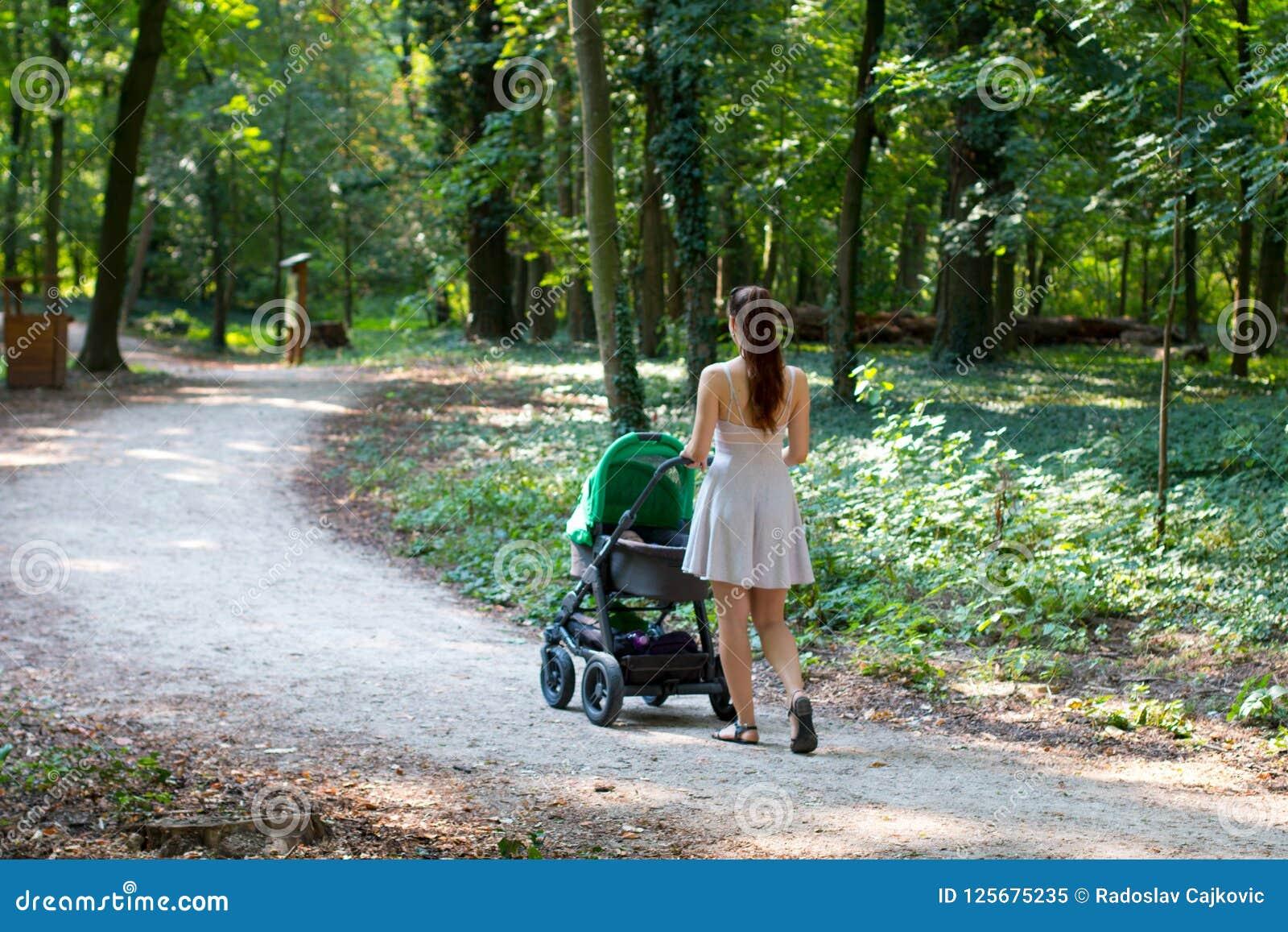 Aardgang met wandelwagen, achtermening van jong wijfje in mooie kleding die op de weg met haar baby in de kinderwagen lopen